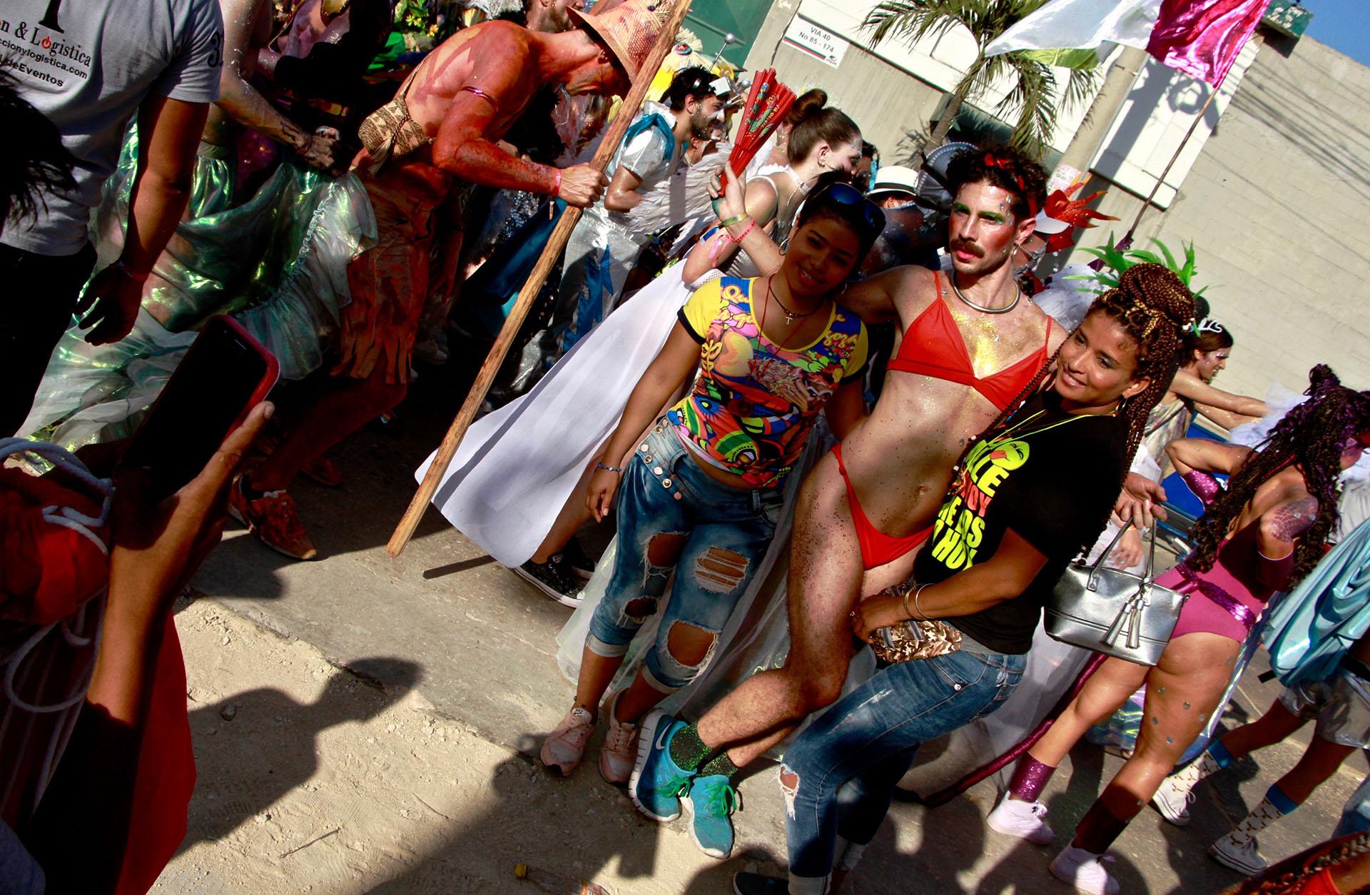 Dos asistentes al desfile se saltaron la valla para tomarse una foto con uno de los bailarines de la comparsa La Puntica No Ma'