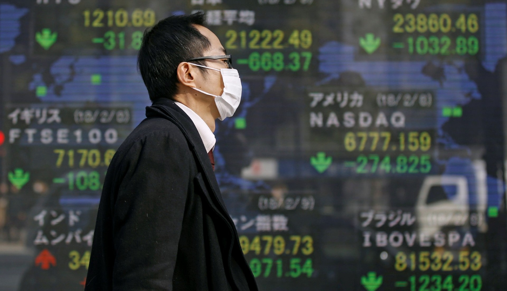 Un ciudadano camina junto a un tablero digital con los valores bursátiles, la mayoría en caída (Reuters)