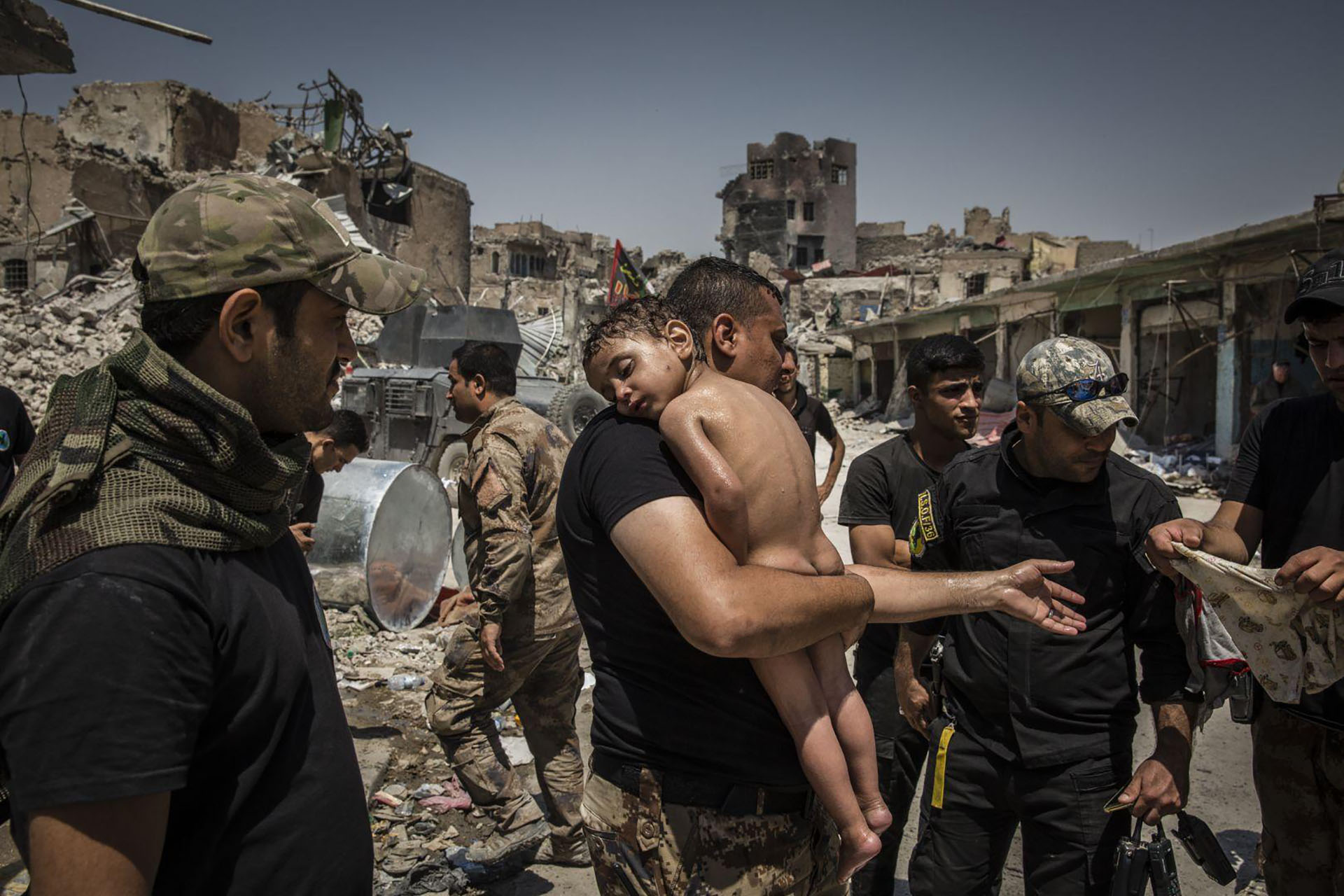 The Battle for Mosul – La batalla por Mosul: foto nominada para la Foto del Año en el concurso de fotografía de World Press. Un joven no identificado, que fue trasladado de la última zona controlada por ISIS en la Ciudad Vieja por un hombre sospechoso de ser militante, es atendido por soldados de las Fuerzas Especiales iraquíes. (Ivor Prickett, Irlanda)