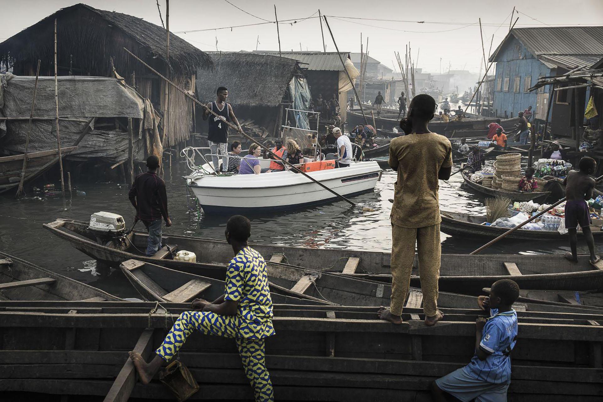 Lagos Waterfront Under Threat – La ribera de Lagos bajo amenaza: un barco con expatriados de Lagos Marina es conducido a través de los canales de la comunidad de Makoko – un antiguo pueblo pesquero que se ha convertido en un enorme asentamiento informal – a orillas de la Laguna de Lagos, Lagos, Nigeria. (Jesco Denzel, Alemania)