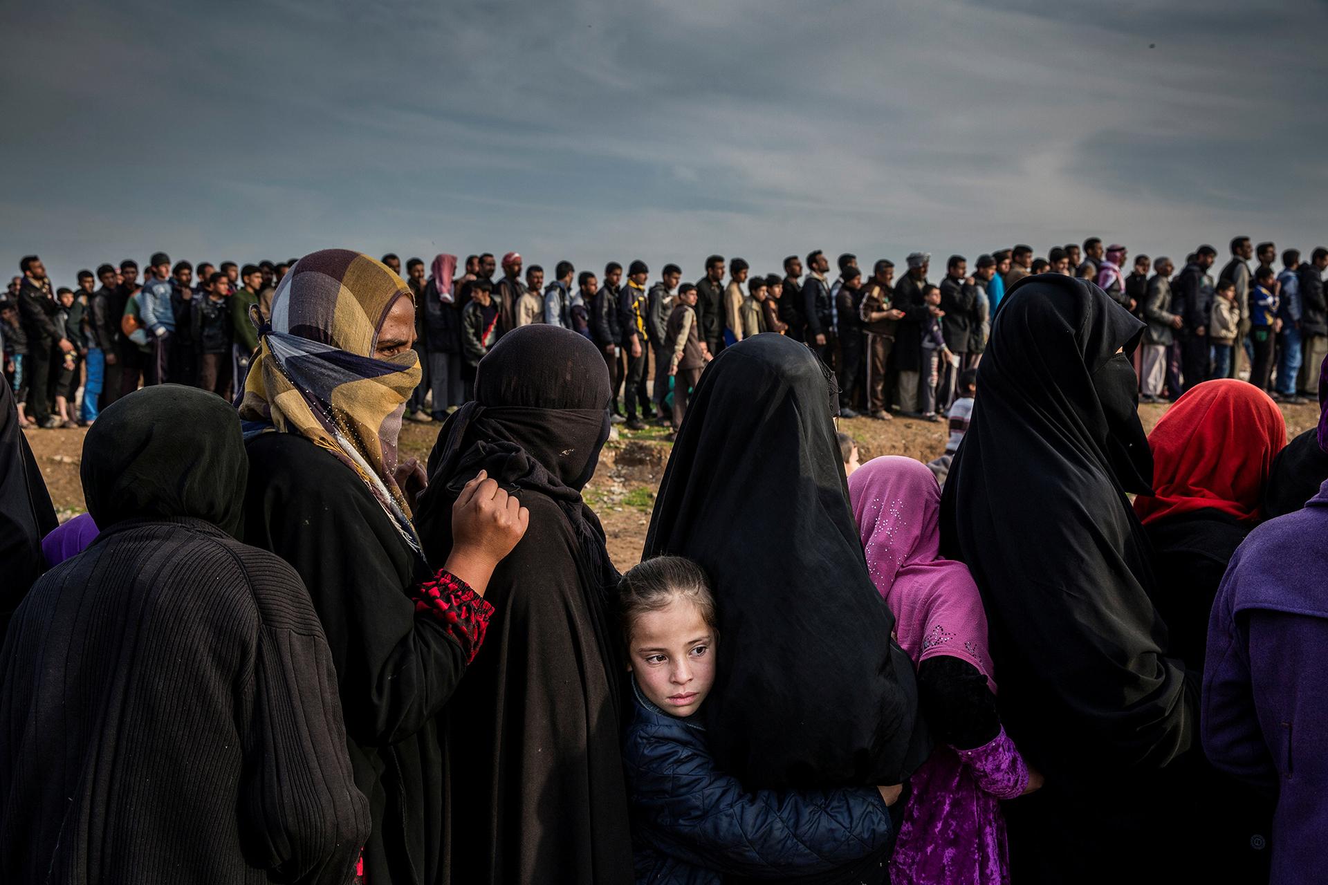 The Battle for Mosul – La batalla por Mosul: foto nominada para la Foto del Año en el concurso de fotografía de World Press. Los civiles que habían permanecido en el oeste de Mosul después de la batalla para tomar la ciudad se paran en fila para recibir ayuda en el barrio de Mamun. (Ivor Prickett, Irlanda)