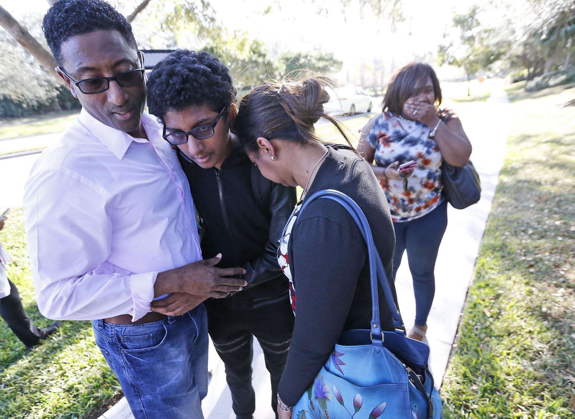Un estudiante junto con sus padres luego de la masacre (AP)