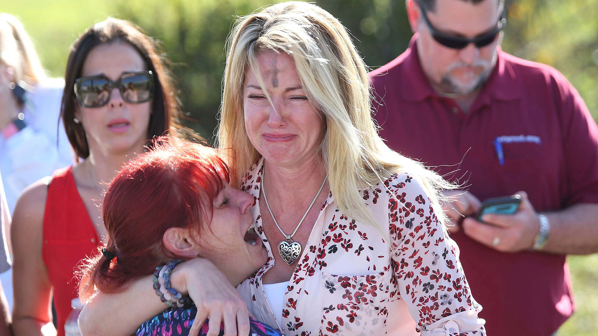 Desconsoladas, una madre y su hija lloran en las afueras de Marjory Stoneman Douglas (AP)