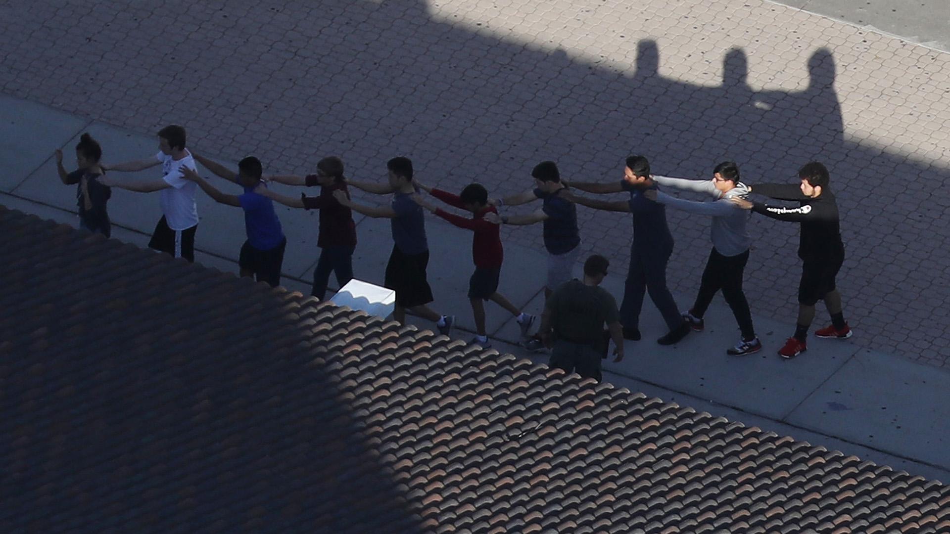 Una fila de alumnos evacuan en fila el instituto. (AFP)