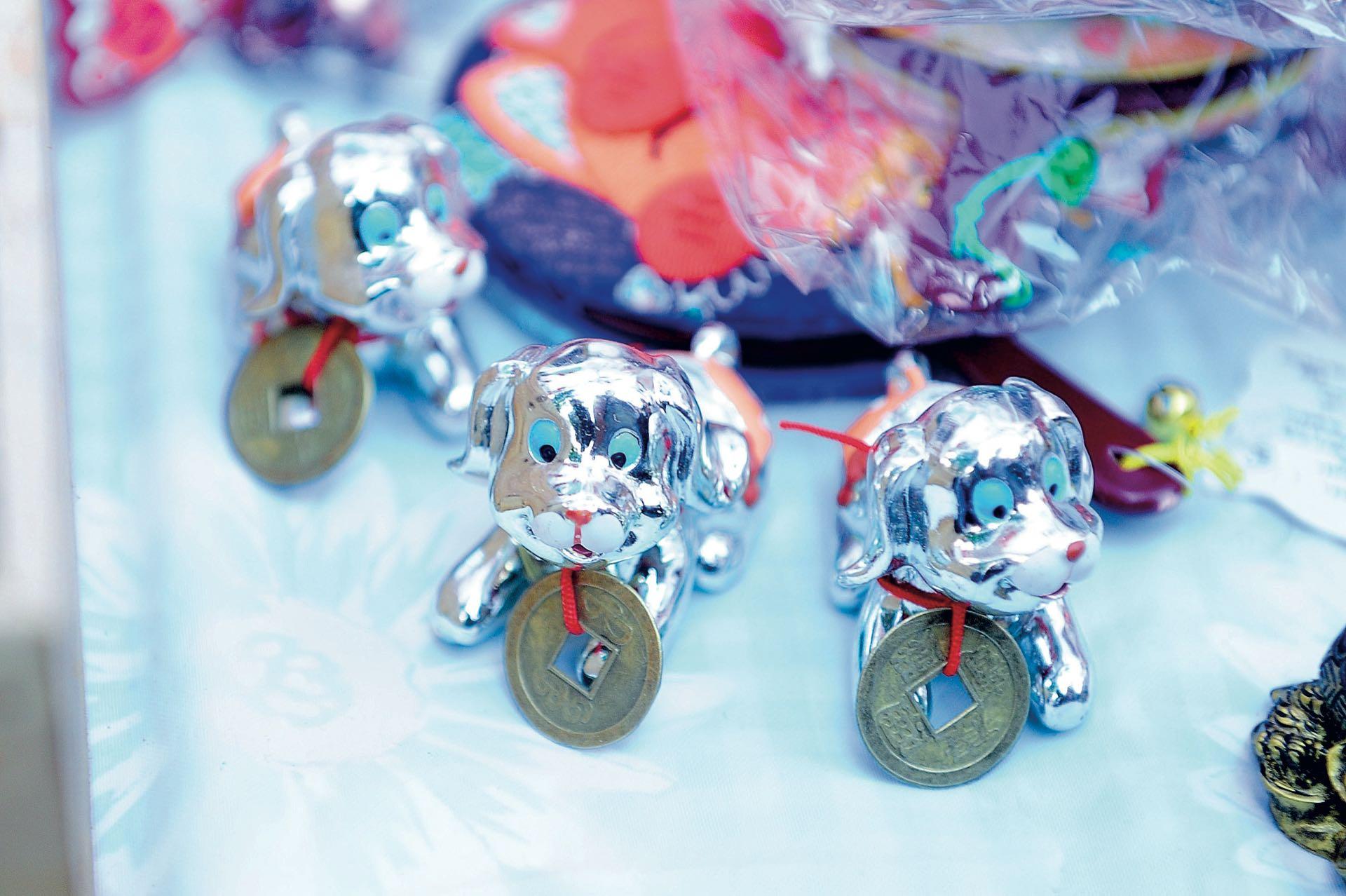 Los más vendidos: los perritos con la clásica moneda china en el cuello. (Fotos: Fabián Mattiazzi y Télam)