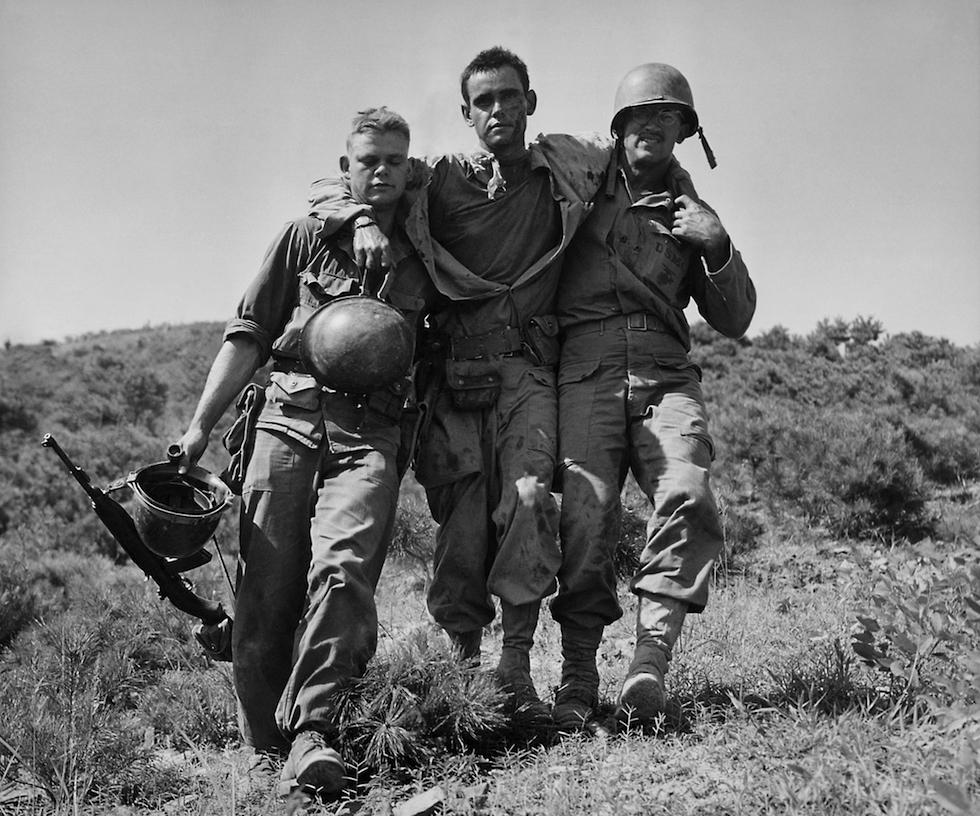Un marine herido ayudado por dos compañeros en Nakdong, en Corea del Sur, agosto de 1950(AP Foto/Max Desfor, File)