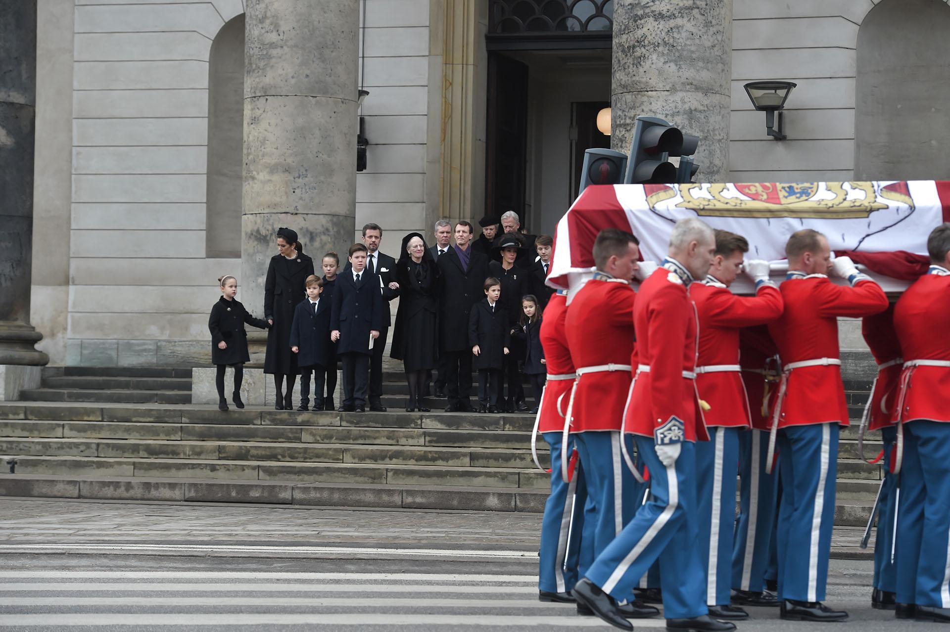 La familia real de Dinamarca observa a los soldados que llevan el féretro y que contiene los restos del príncipe Enrik, tras finalizar el servicio religioso en su memoria en la capilla del Palacio de Christiansborg, en Copenhague