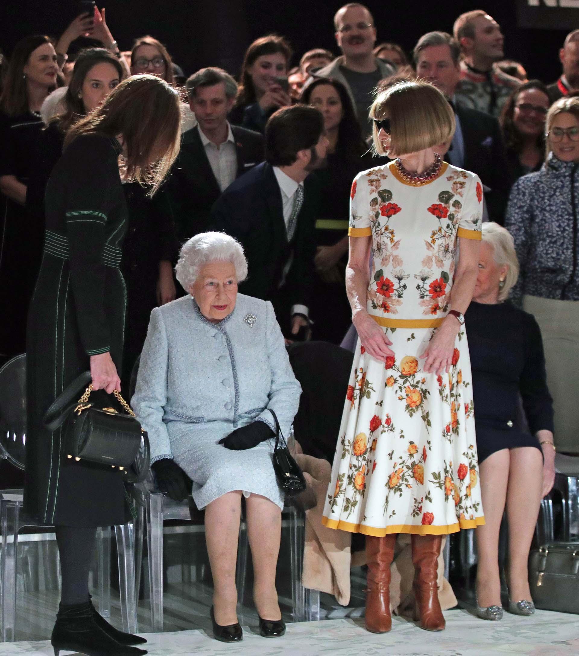Una de las mujeres más poderosas del ambiente comparte lugar junta a la Reina Isabel II, expectantes antes de la presentación de la firma italiana: Gucci
