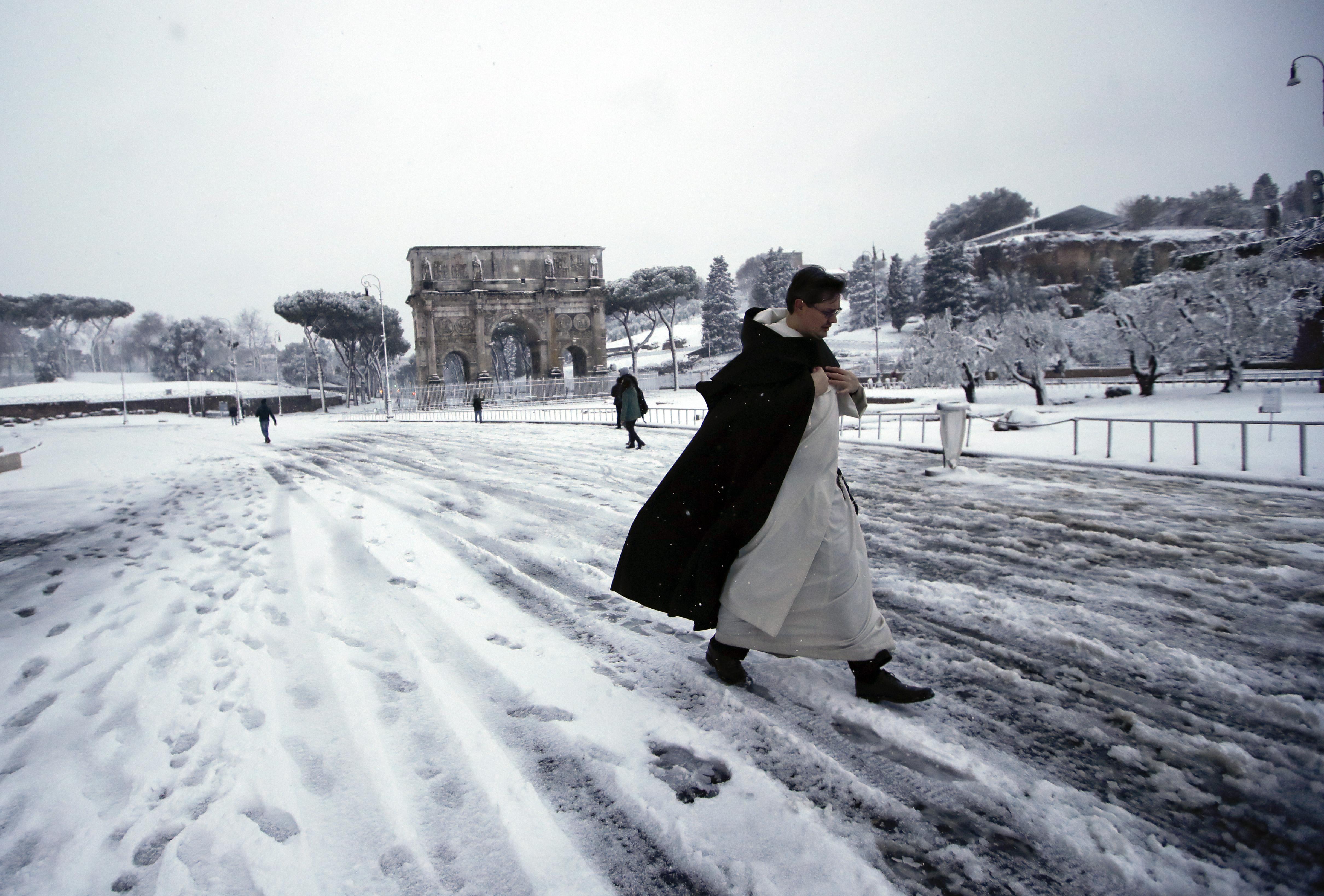 Un cura caminando cerca del Arco de Constantino (AP/Alessandra Tarantino)