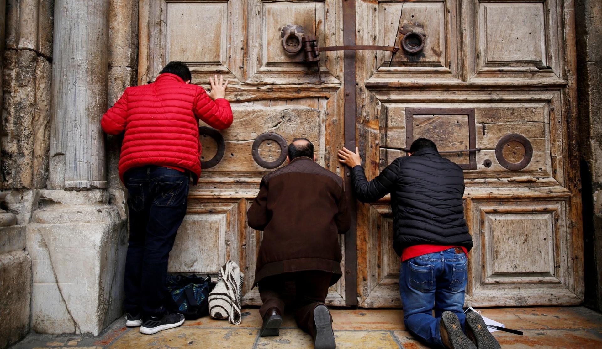 Peregrinos se arrodillan ante las puertas cerradas del templo (Reuters)