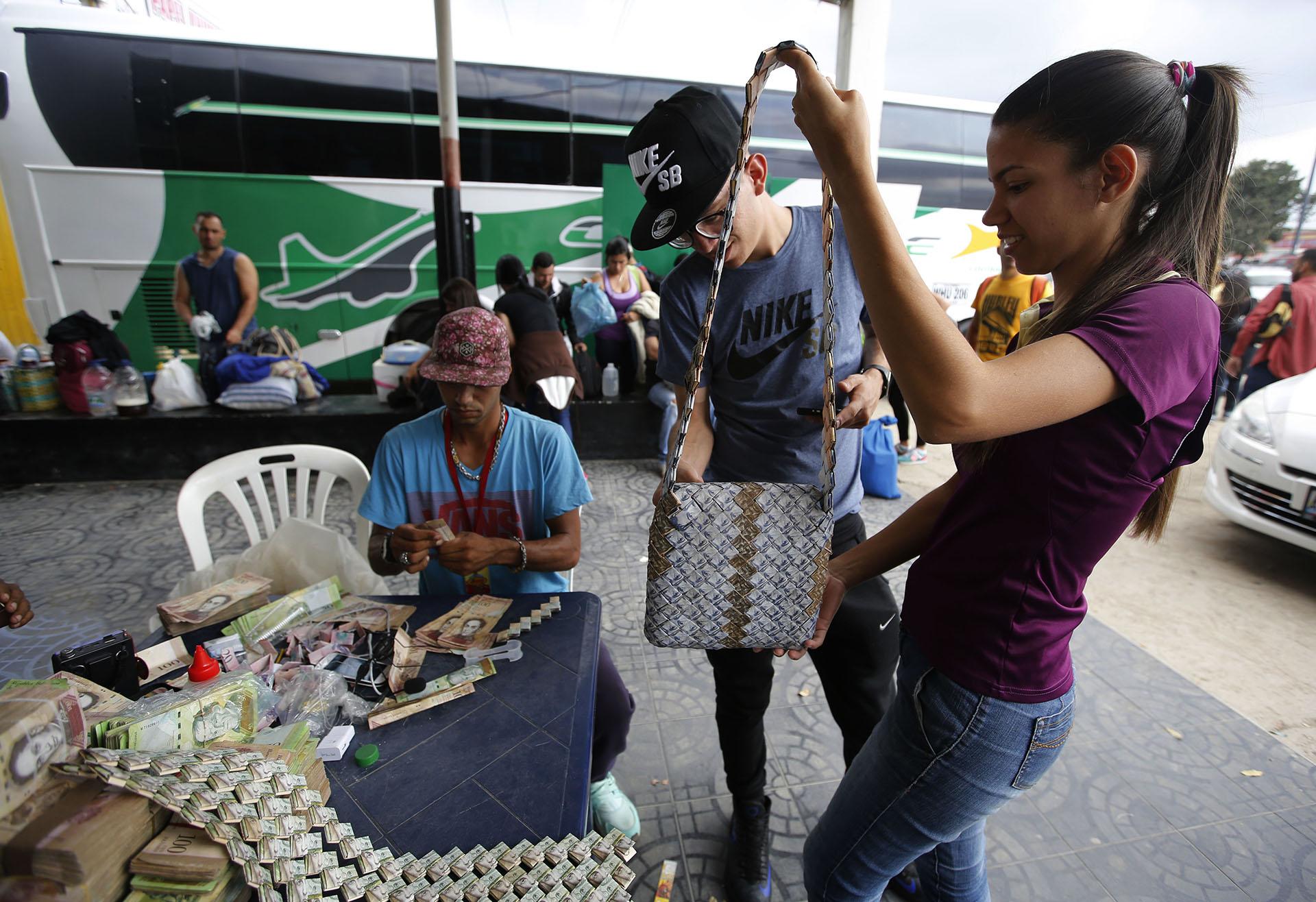 clientes observan un bolso hecho con billetes, vendido por entre 10 y 15 dólares