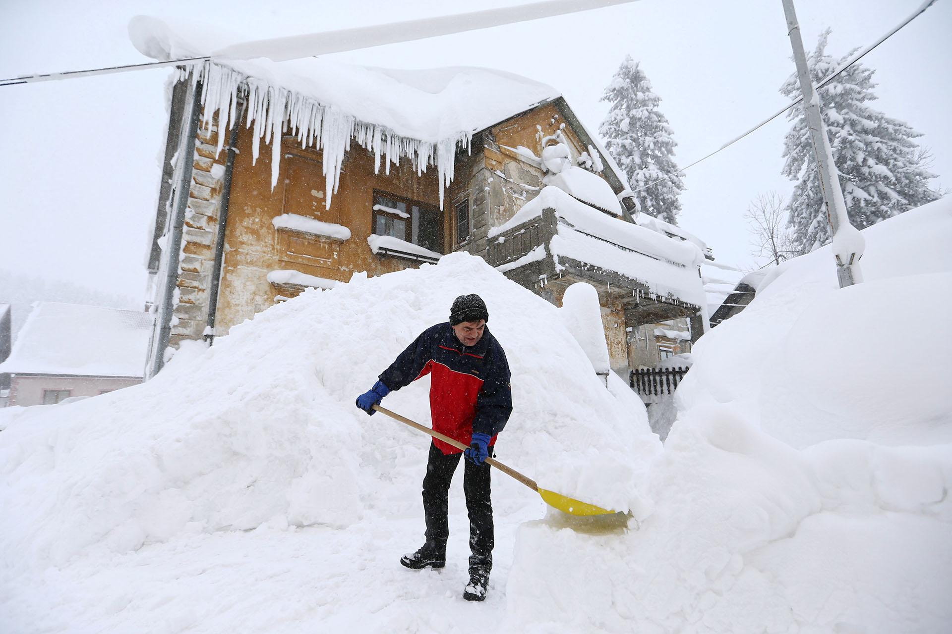 Un hombre abre un camino entre la nive en Delinice, Croacia
