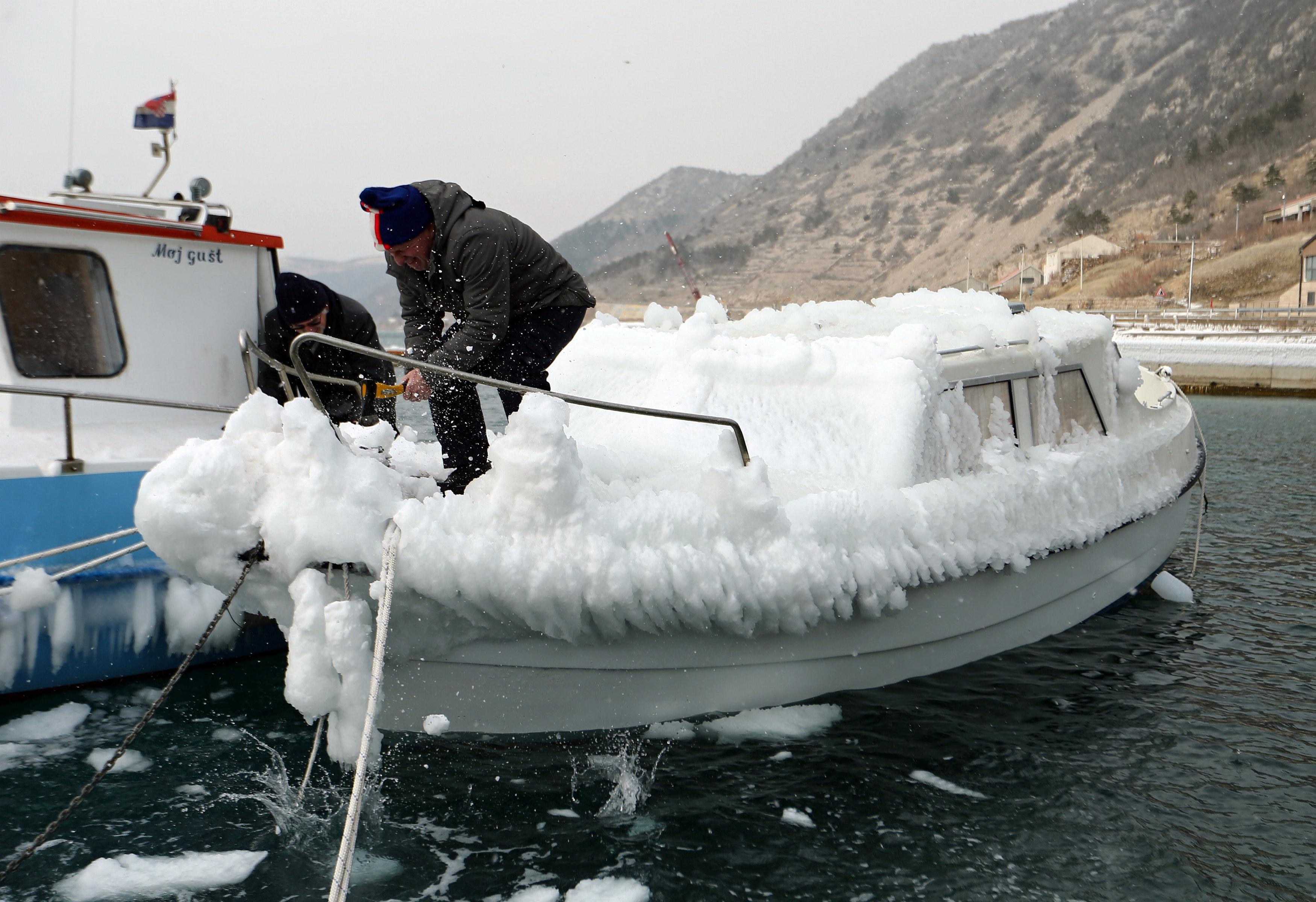 Un hombre limpia su barco enBakarac, Croacia (REUTERS/Antonio Bronic)