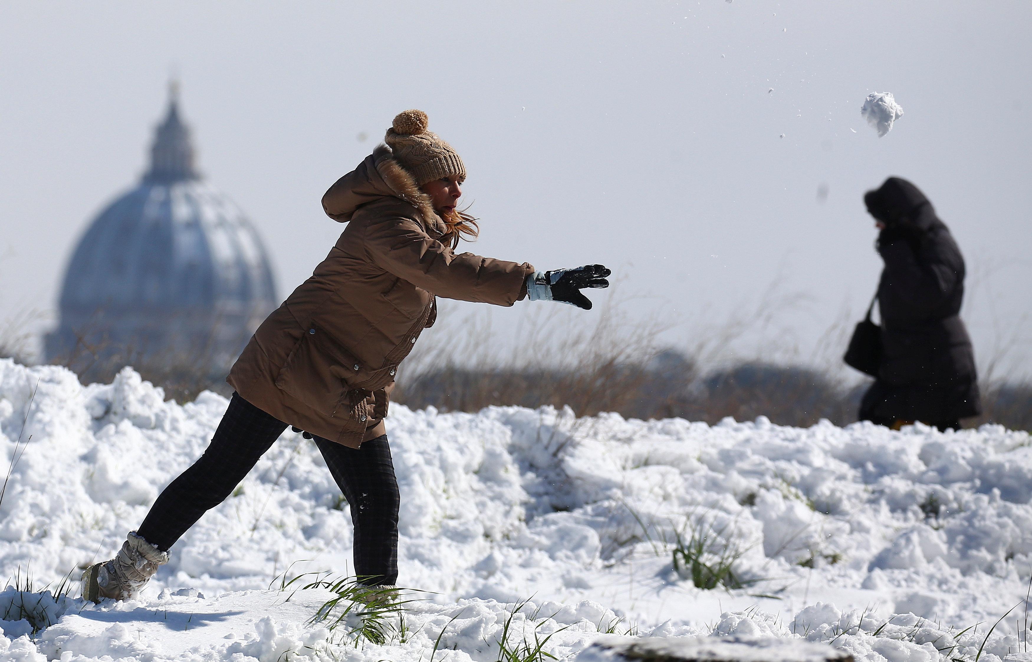Una mujer lanza una bola de nieve frente a la cúpula de San Pedro en Roma(REUTERS/Alessandro Bianchi)