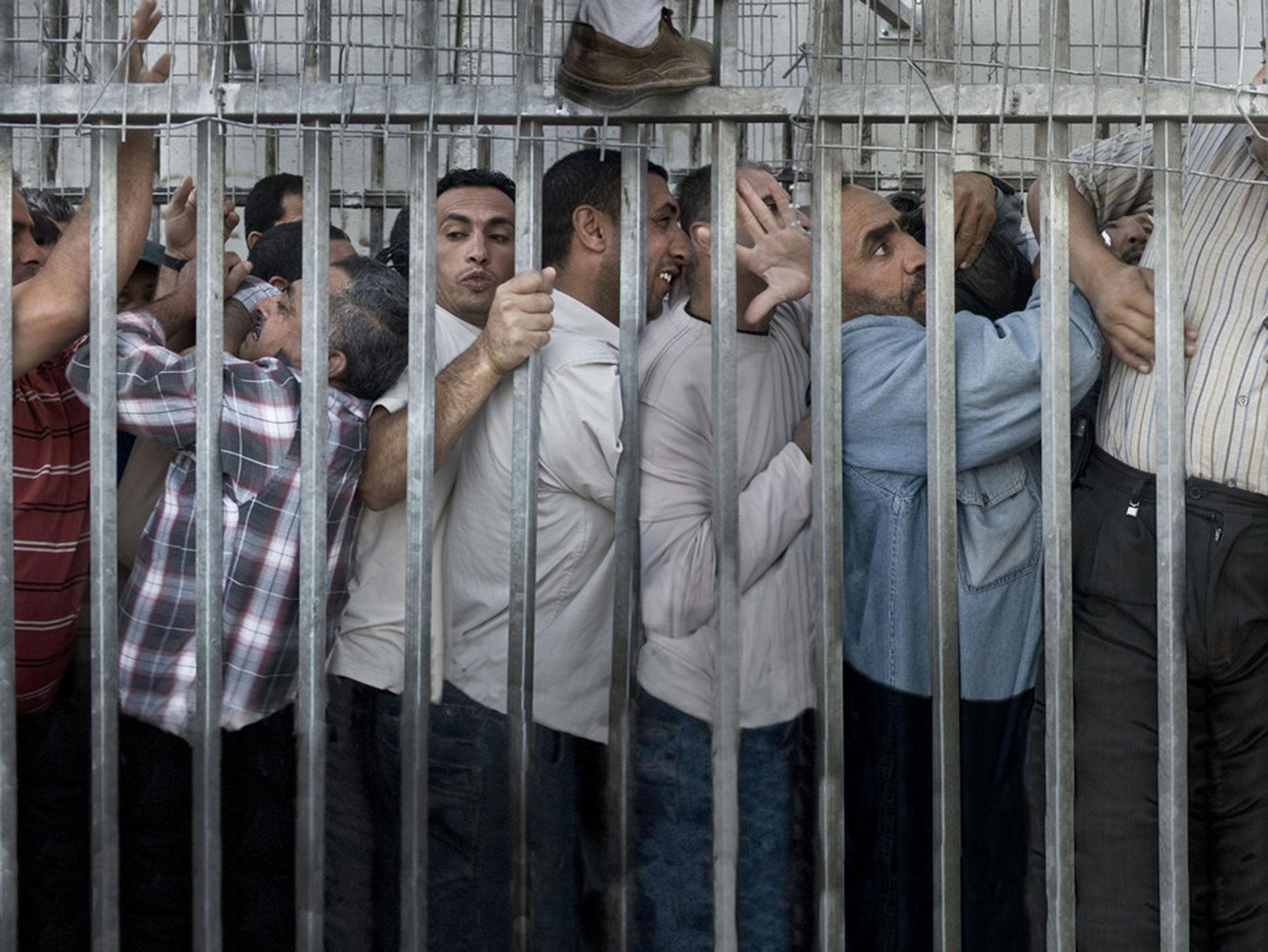 """Competencia """"Profesional"""" – Categoría """"Creativo"""": Todos los días, antes del atardecer, miles de trabajadores palestinos pasan entre dos y cuatro horas amontonados para cruzar el llamado """"CheckPoint 300"""", que divide Belén y Jerusalén, para trabajar en Jerusalén y sus alrededores. (Gentileza Sony World Photography Awards)"""