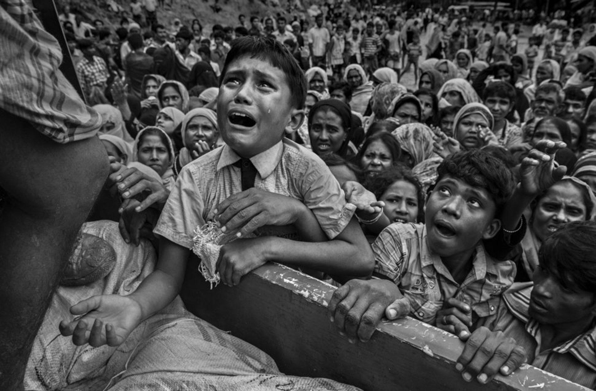 """Competencia """"Profesional"""" – Categoría """"Noticias y Asuntos de Actualidad"""": un niño refugiado de Rohingya desesperado por ayuda llora mientras sube a un camión que distribuye ayuda a una ONG local cerca del campamento de refugiados de Balukali el 20 de septiembre de 2017, en Cox's Bazar, Bangladesh. (Gentileza Sony World Photography Awards)"""