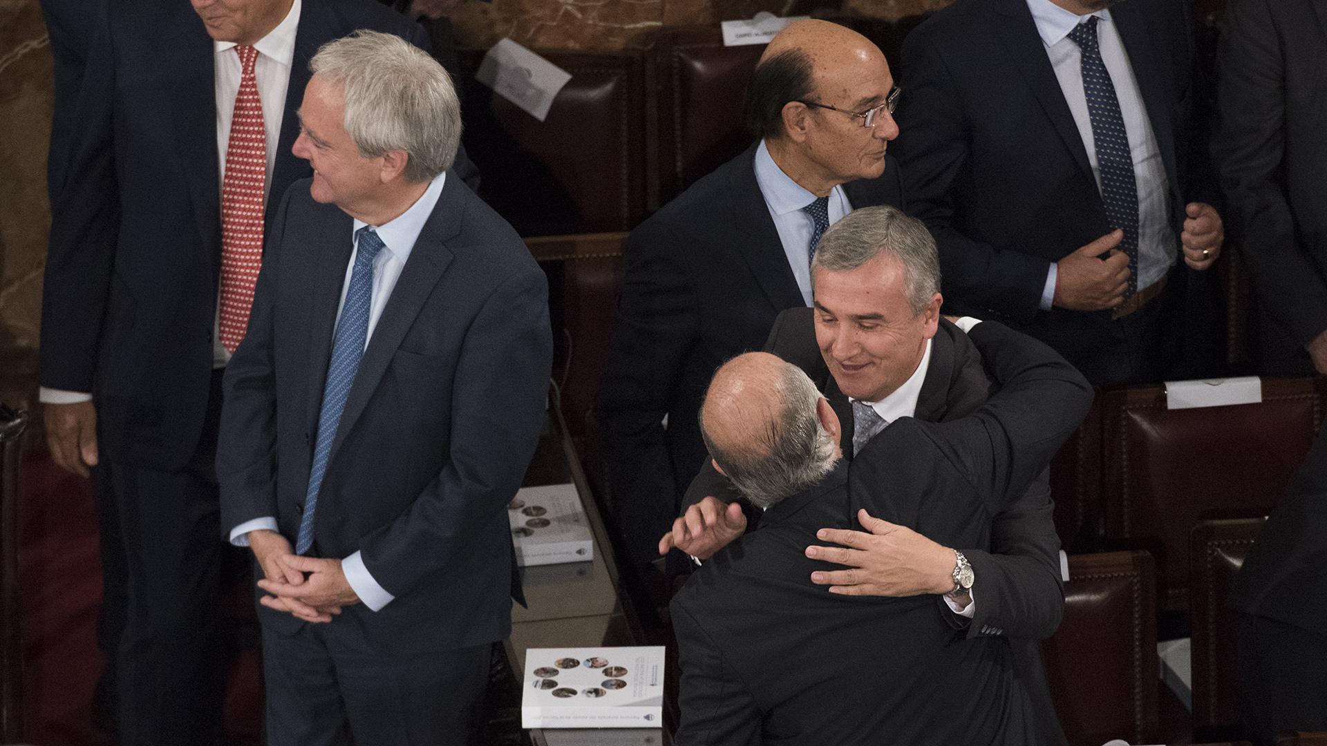 Pinedo rie en el fondo, mientras Gerardo Morales saluda a un legislador