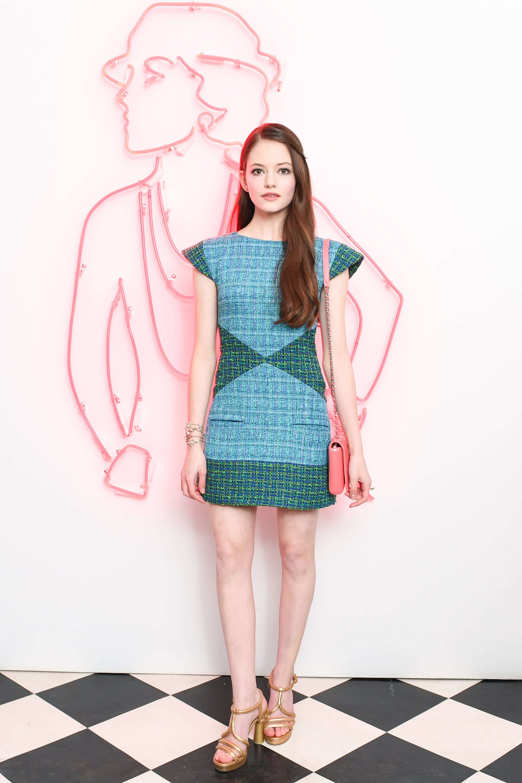 La actriz de 'Crepúsculo' -Mckensie Foy- vistió un diseño de 'tweed' en azul y verde con sandalias doradas y mini bag rosa