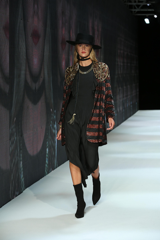 Un clásico saco de pailletes rayado en negro y bordó con hombreras bordadas en dorado acompañando a un vestido de corte asimétrico de seda