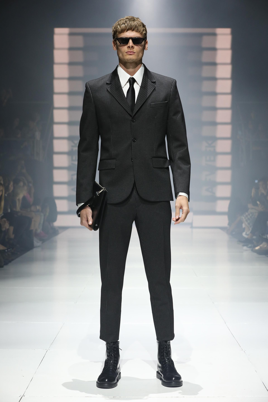 Mis Íntimos Amigos. Clásico traje a rayas negro, con camisa blanca y corbata de seda negra. El detalle fashionista: el corte crop del pantalón y las botas de charol