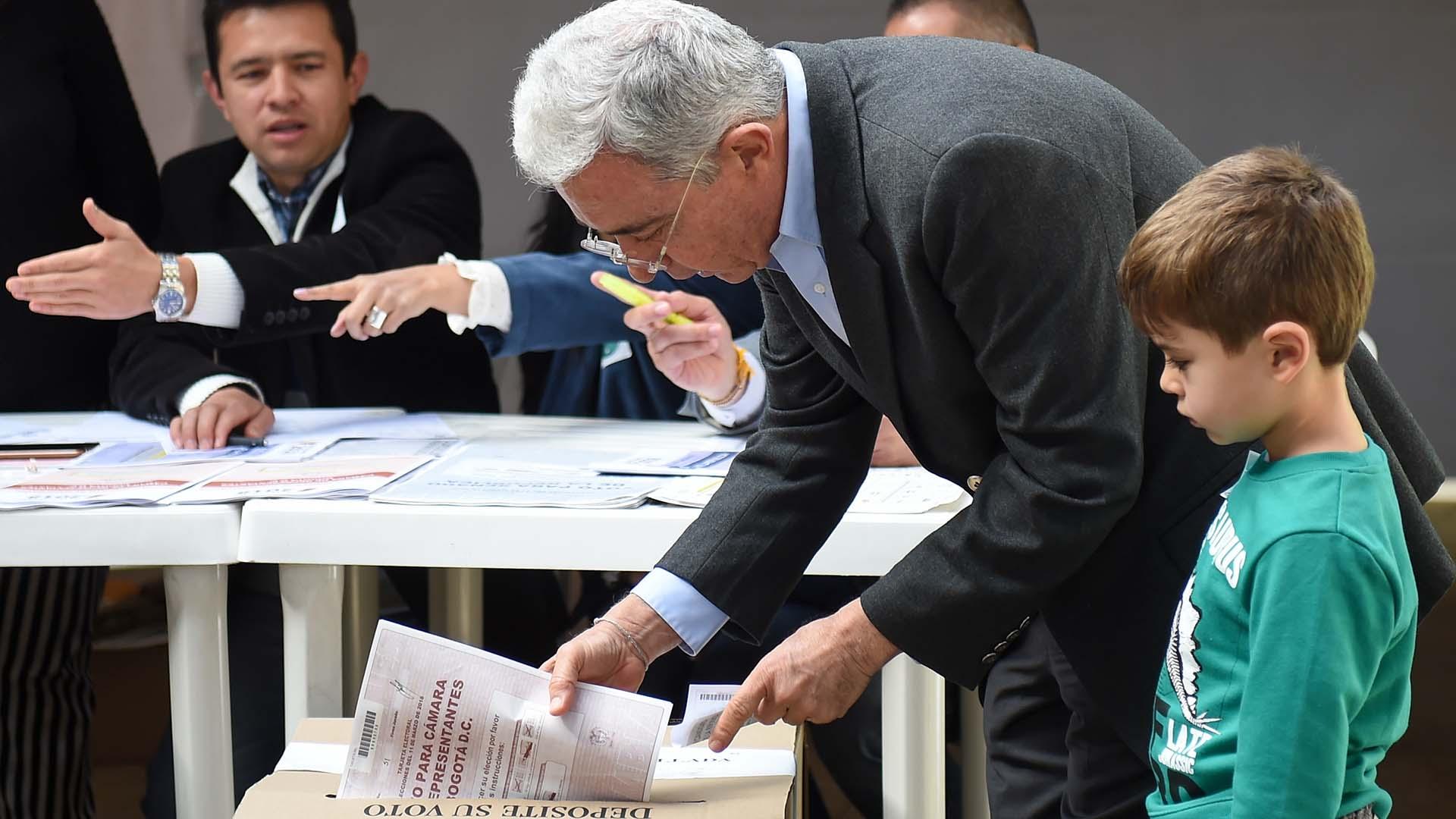 Álvaro Uribe votó junto a su nieto (AFP)