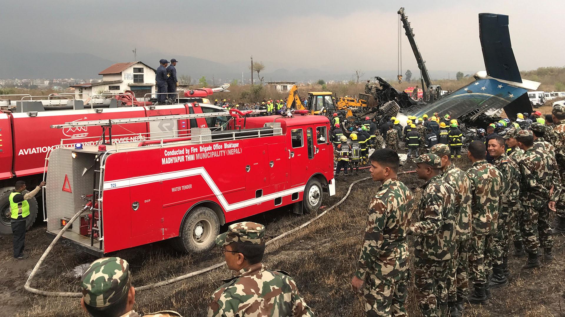 Los vehículos de los bomberos que apagaron el incendio del avión y los militares que cercaron el lugar tras el accidente