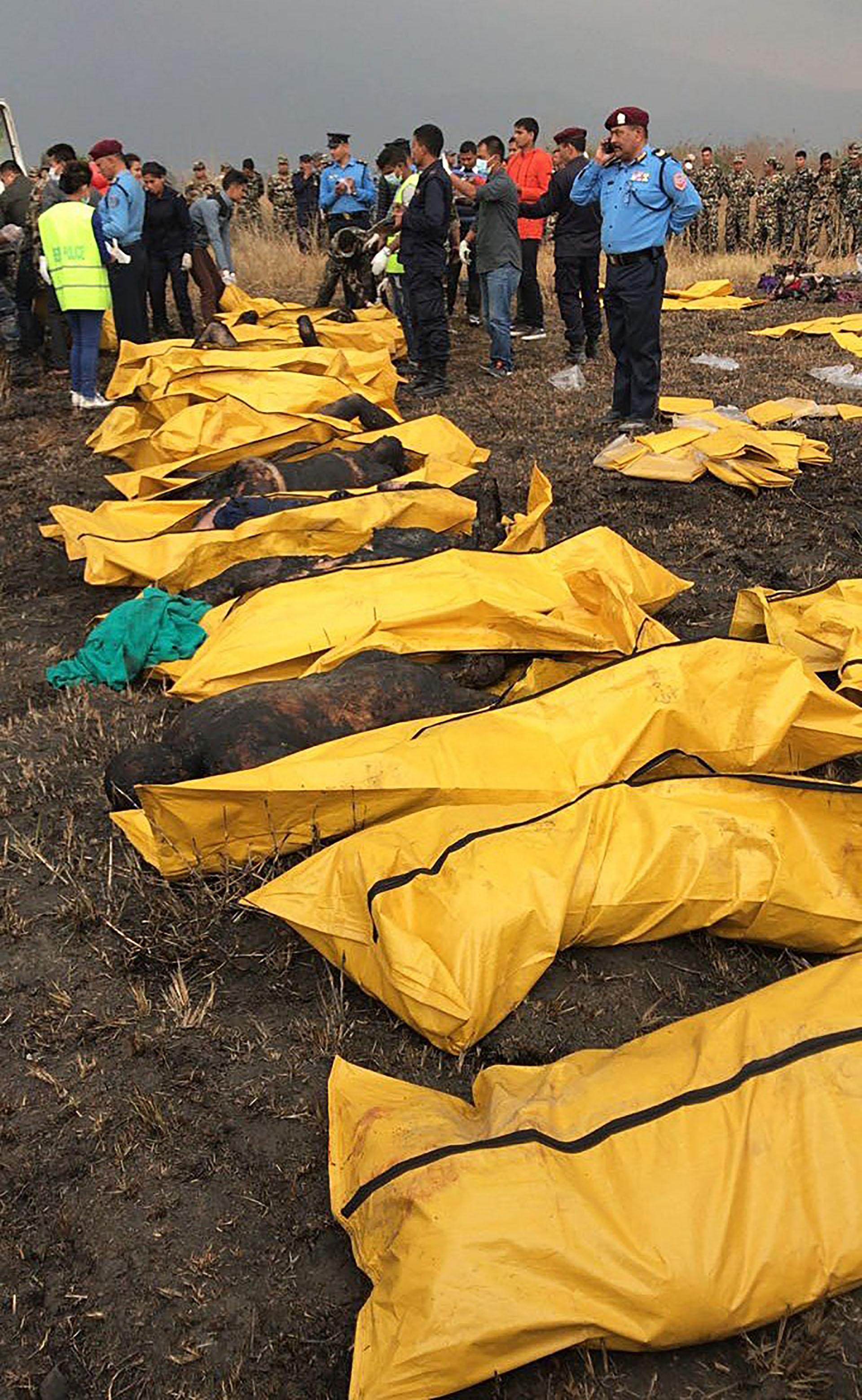 Los cadáveres calcinados de varias víctimas tras ser recuperados por los equipos de rescate de entre los restos del avión que se estrelló en el aeropuerto de Katmandú