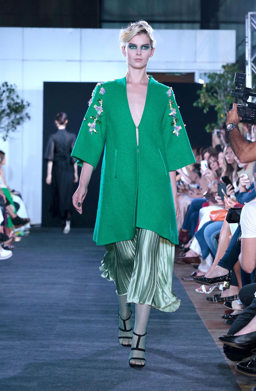 Tapado de paño en verde esmeralda con bordado de flores, un must. Debajo, una falda midi plisada en verde pastel metalizado