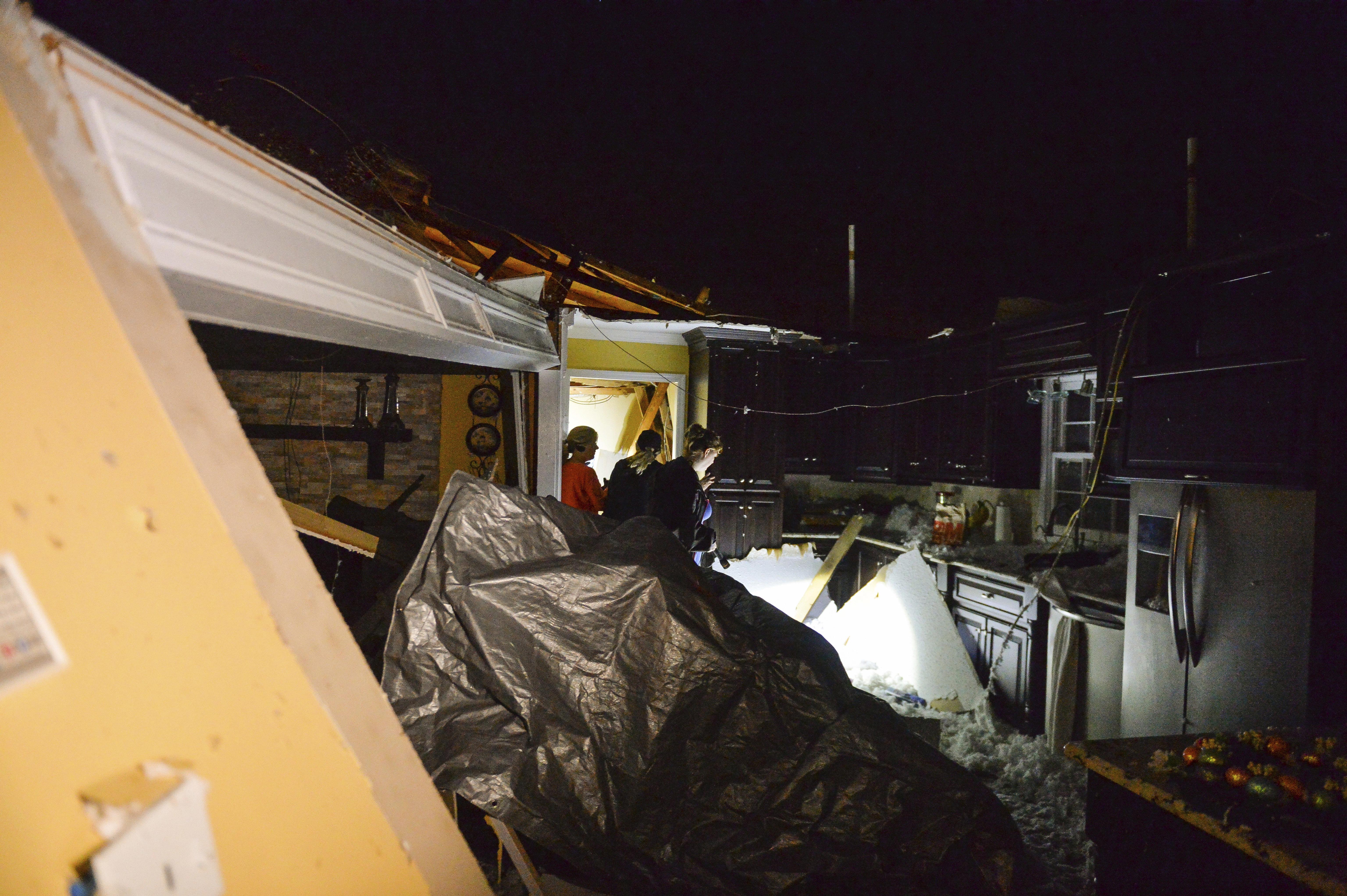 Una familia inspecciona los daños provocados por un tornado en Ardmore, Alabama (Crystal Vander Weit/The Decatur Daily via AP)