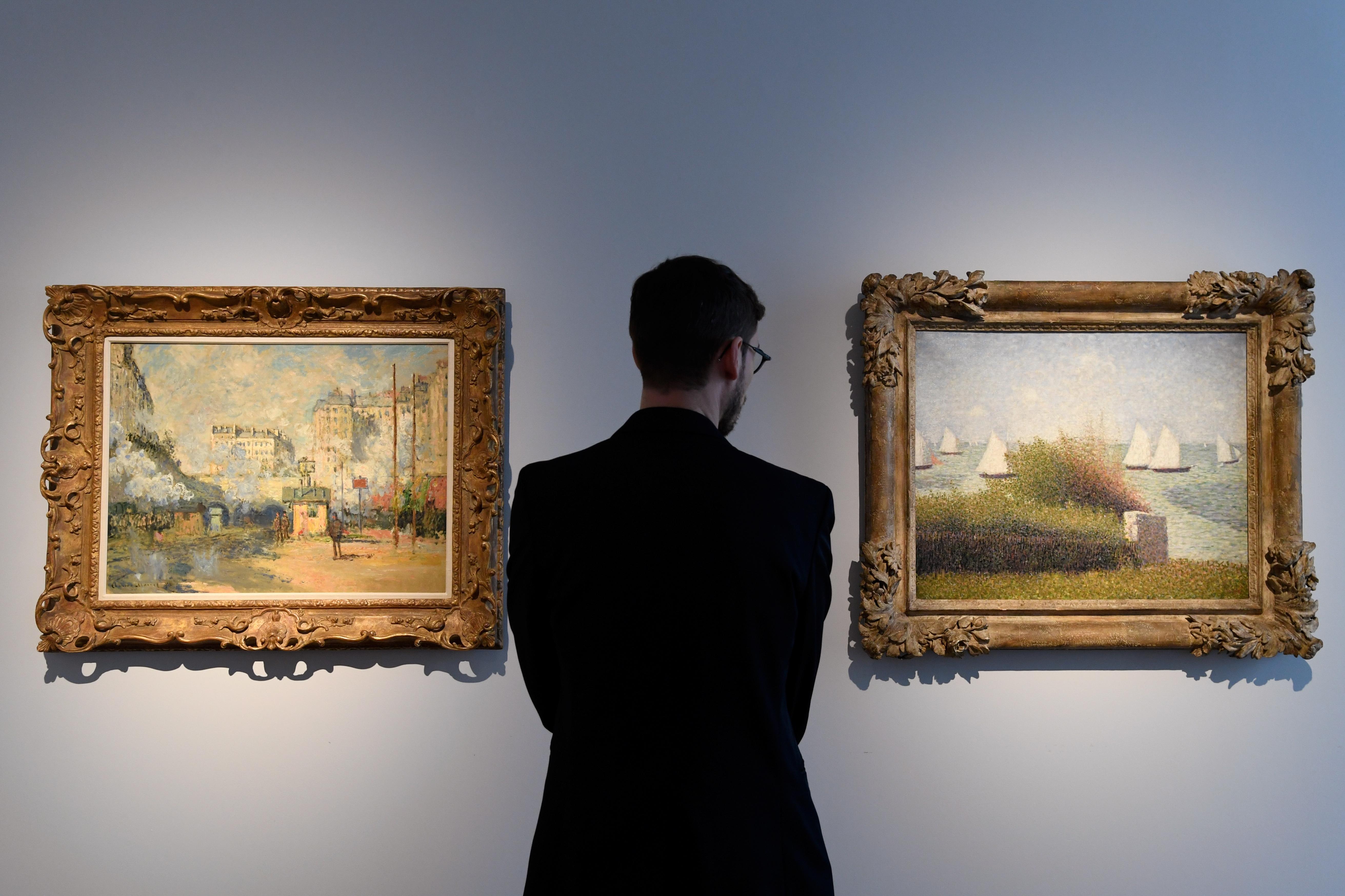 """Un hombre observa una de las famosas pinturas de Saint-Lazare del francés Claude Monet (1877), y la obra """"La rade de Grancamp"""" (1877) de Georges Seurat, estimadas en hasta USD 25 millones"""
