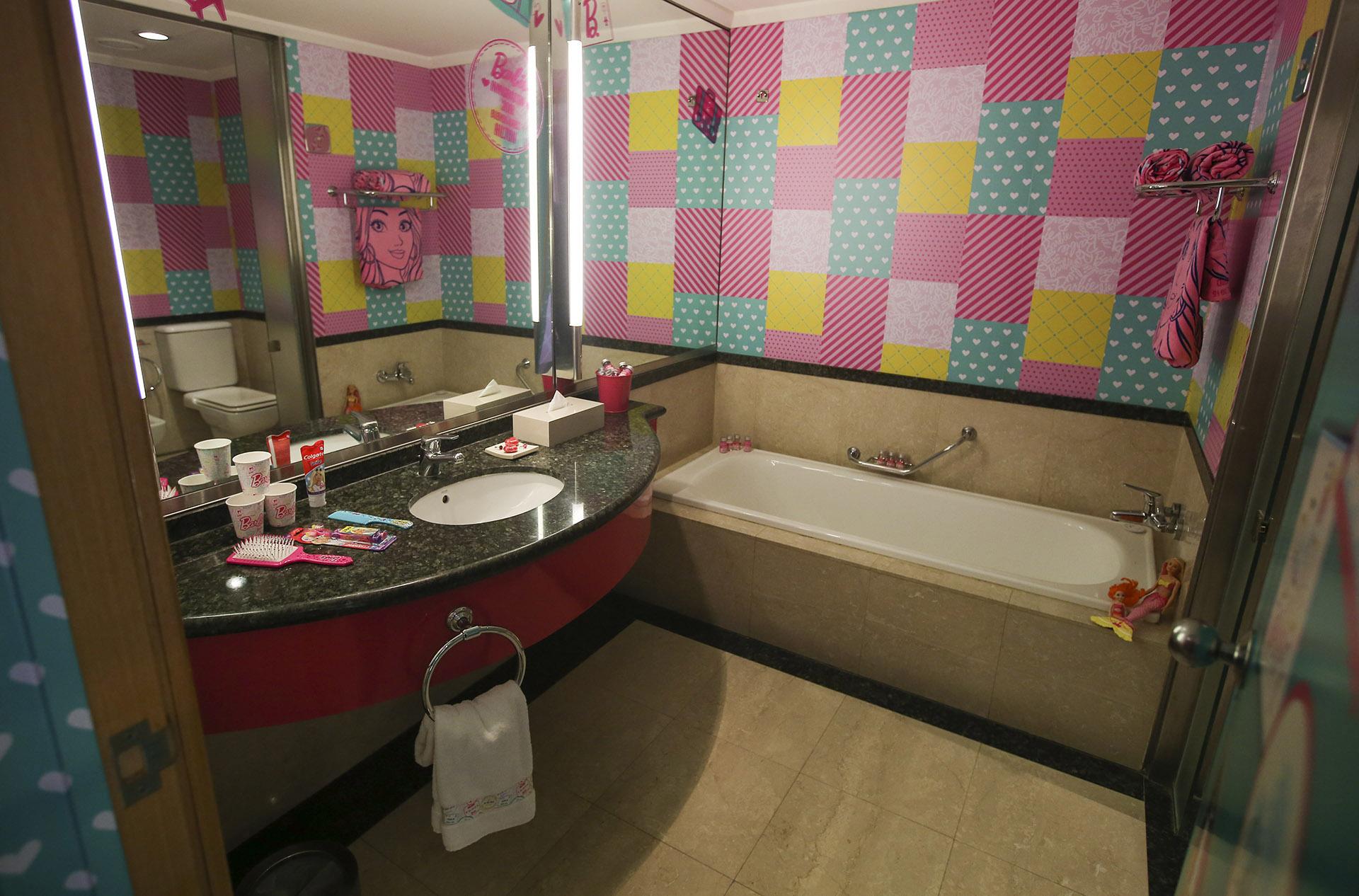 El baño completo con bañadera incluida, toallas y azulejos intervenidos
