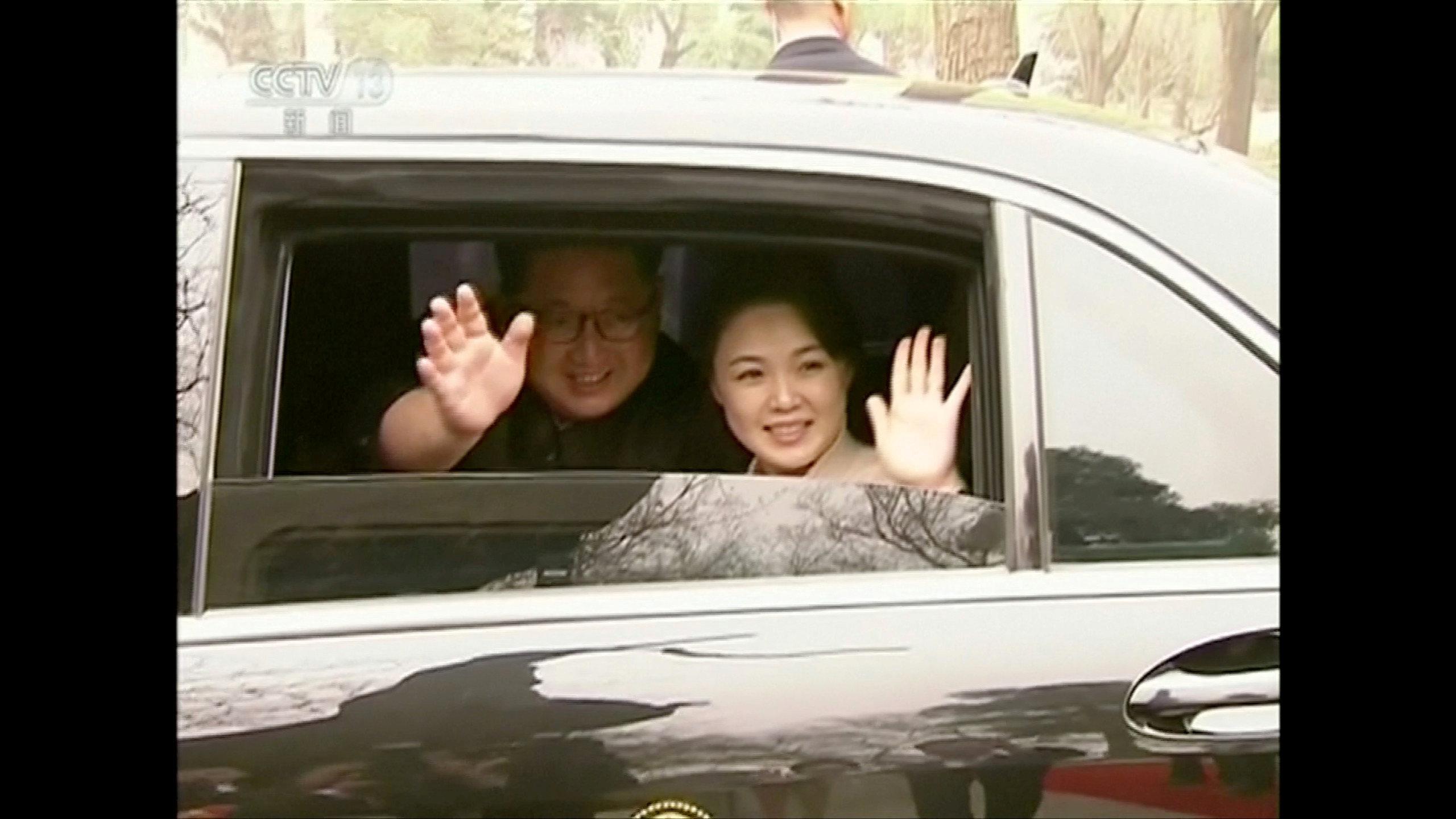 Kim Jong Un y Ri Sol Ju saludan sonrientes desde el vehículo que los trasladó en Beijing