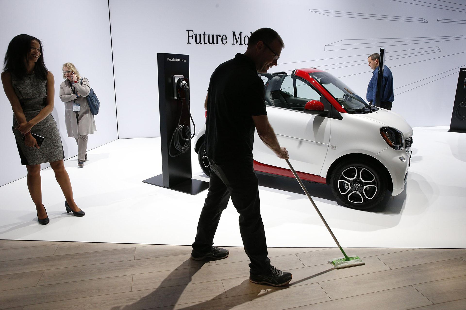 Unempleado prepara el stand de Daimler AG para la apertura del Salón de Nueva York, que abrirá sus puertas al público del 30 al 8 de abril. De fondo, se luce un Smart car Fortwo Electric Drive que expone las ideas de movilidad inteligente de la marca