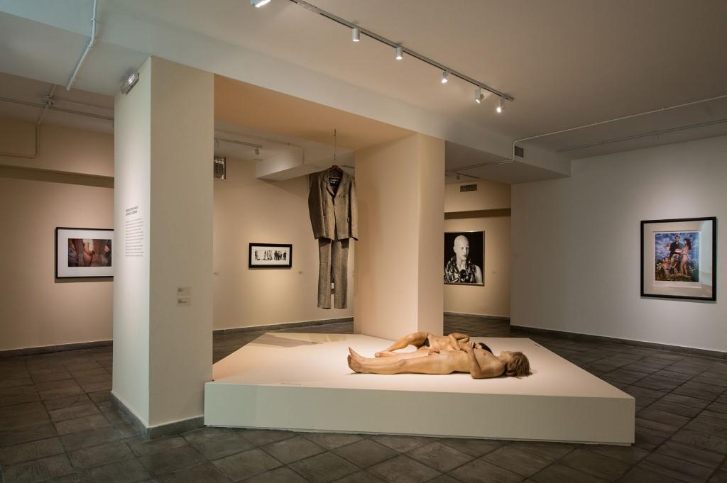 Sobre la tarima los cuerpos John De Andrea El traje es de Joseph Beuys La fotografía que se ve sobre la pared derecha es Jeff Koons La foto del fondo a la derecha es Marcos López Detrás de las columnas a la izquierda Cindy Sherman