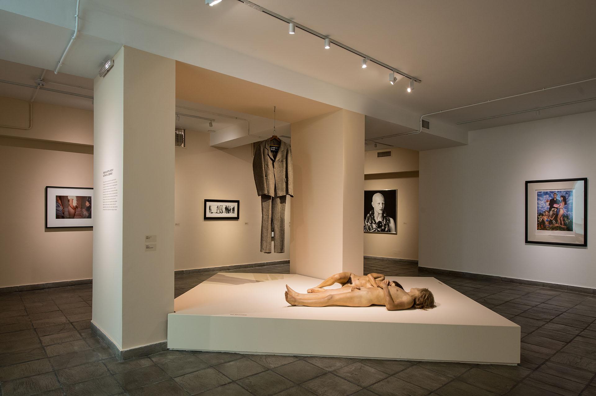 Sobre la tarima, los cuerpos de John De Andrea.El traje de fieltro es de Joseph Beuys. La fotografía que se ve sobre la pared derecha es de Jeff Koons.La foto del fondo a la derecha es Marcos López. Detrás de las columnas a la izquierda, Cindy Sherman