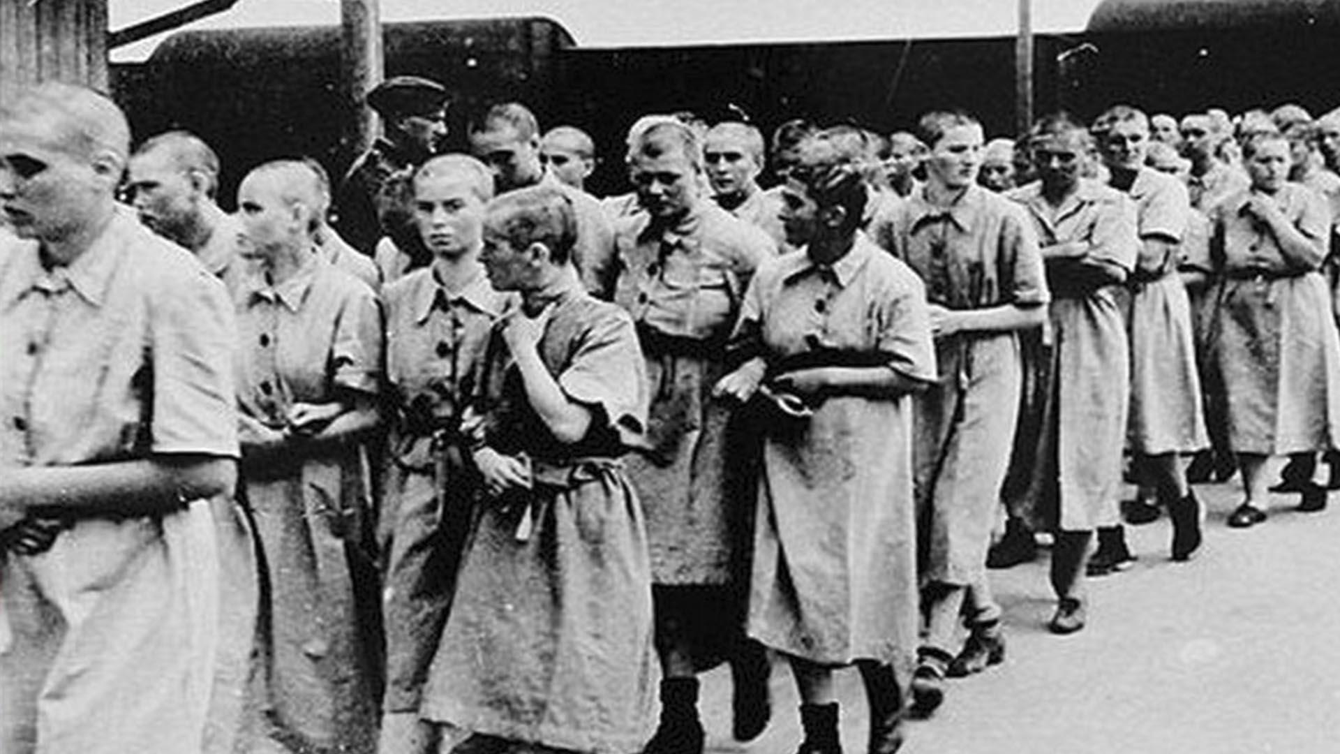 Las prisioneras se desplazan por el campo de concentración. Algunas se toman del brazo. Están desabrigadas y se percibe el frío. Las despojaron hasta del pelo. En los ojos, las miradas perdidas.