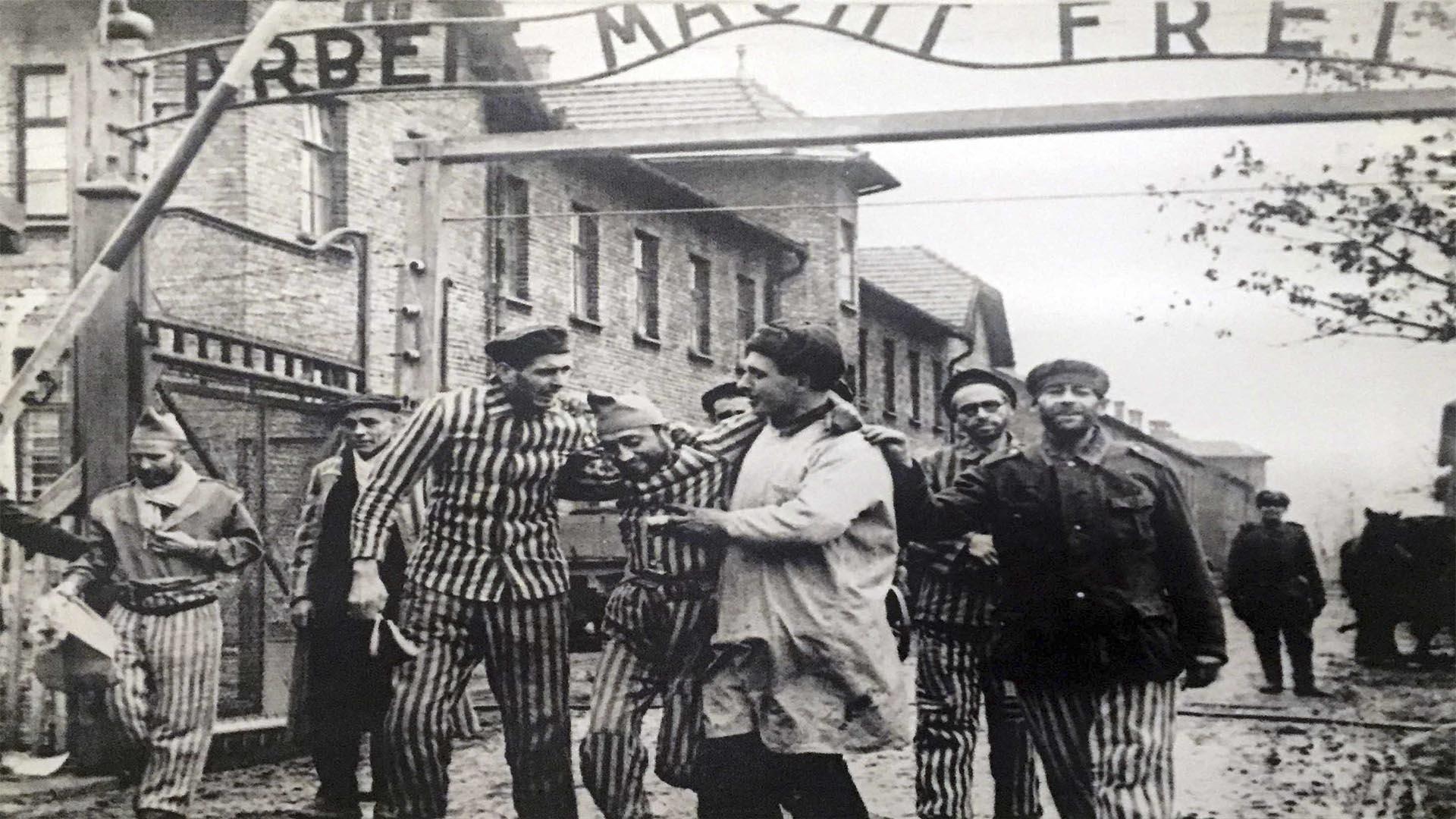 Asoman unas sonrisas. Algunos sobrevivientes luego de la liberación del Campo enmarcados por el cínico pórtico de Auschwitz: Arbeit macht frei (El trabajo los hará libres)