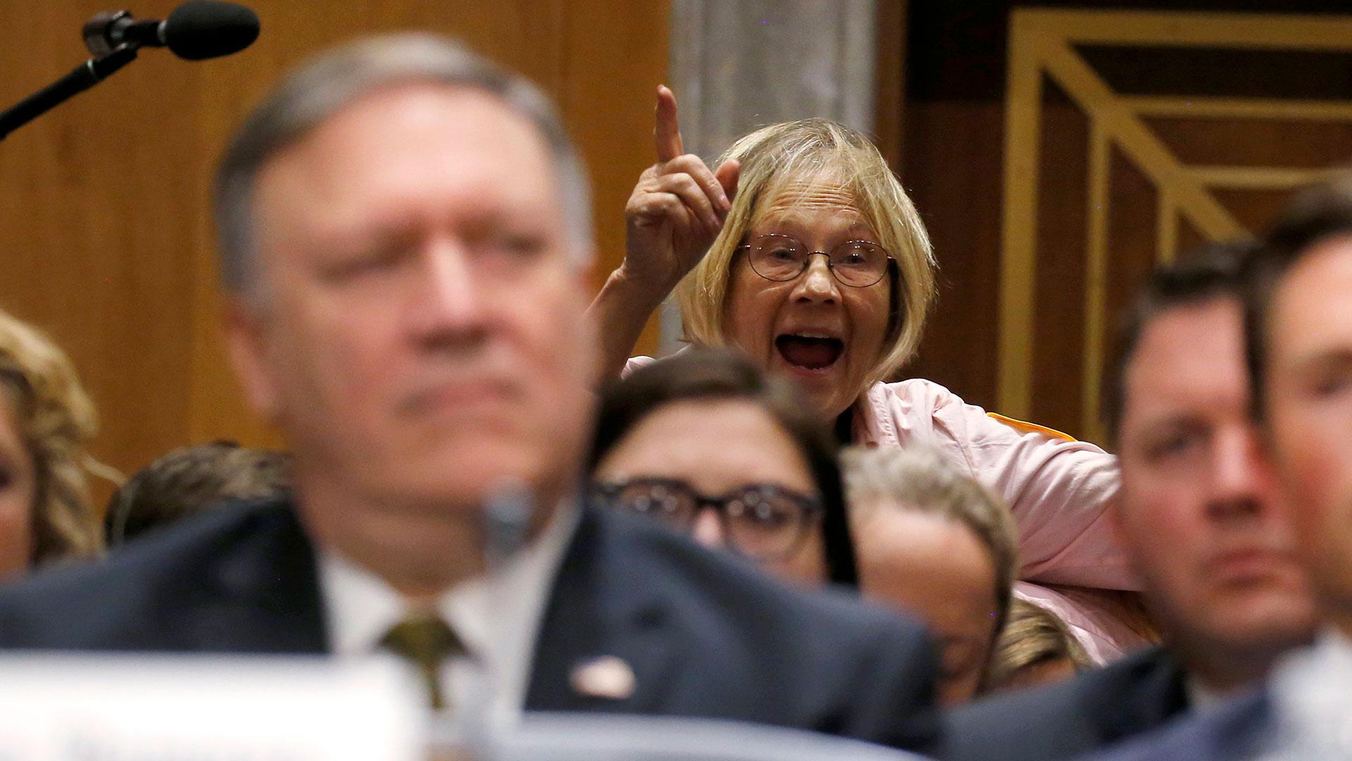 Una mujer grita detrás del actual director de la CIA