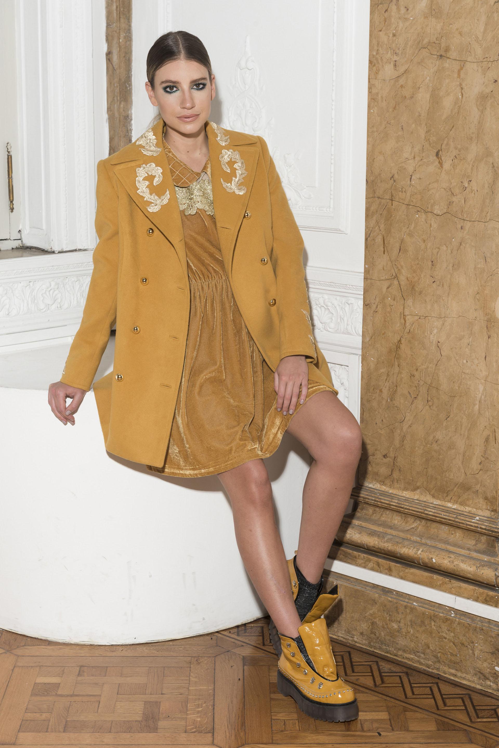 Mostaza total. Tapado de paño con detalles de bordado en hilo de oro con vestido de chiffon con cuello y bordado de flores. Borcegos charolados de Sofía Sarkany