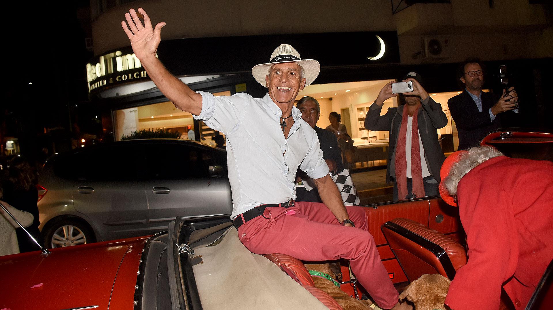 """Saludando a sus invitados sobre un automóvil de colección, así llegó Ricardo Piñeiro a la presentación de su muestra """"Fuego Sagrado"""", en Recoleta"""