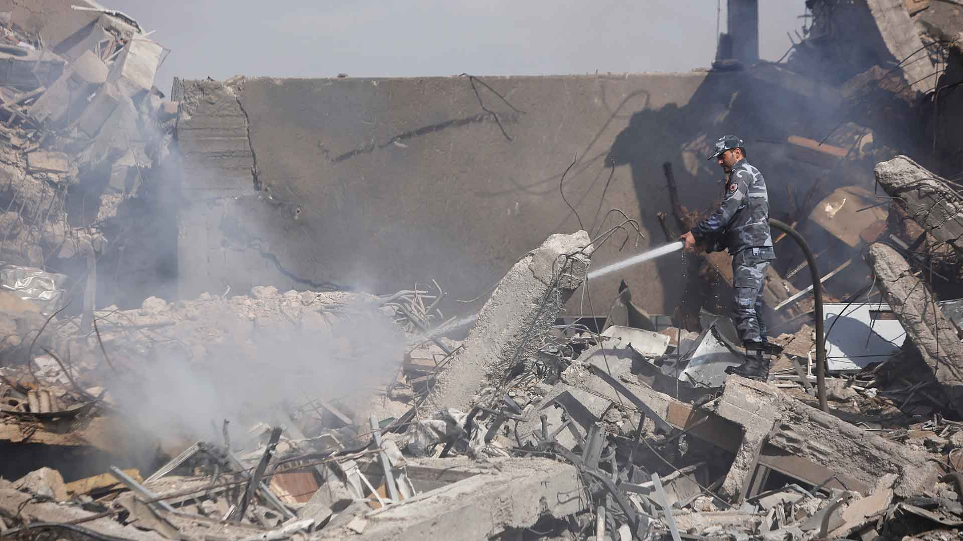 Un soldado sirio apaga las llamas tras el bombardeo contra el Centro de Investigación Científica de Damasco(REUTERS)