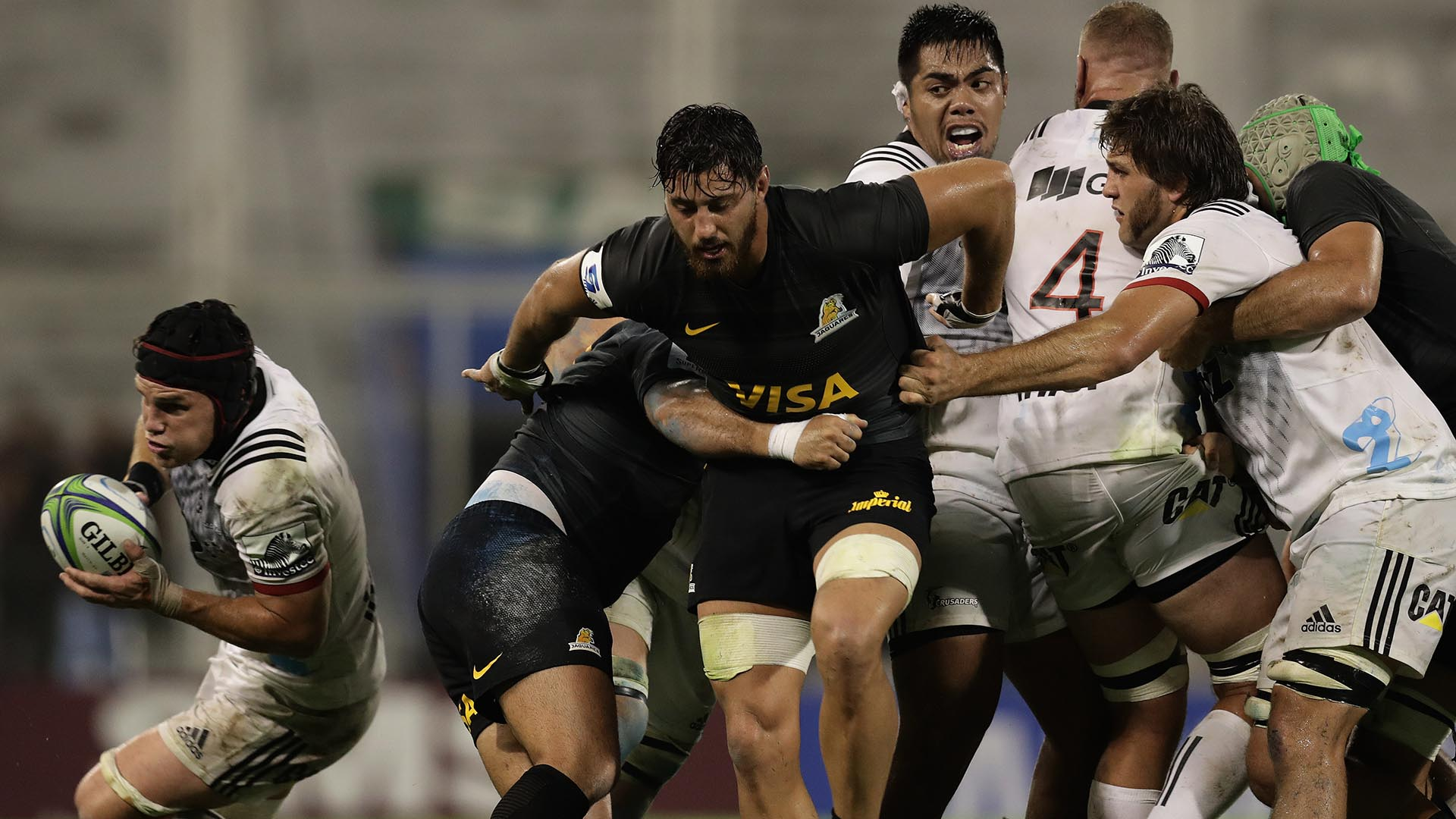 New Zealand's Crusaders flanker Matt Tood (L) runs with the ball past Argentina's Jaguares players during their Super Rugby match at Jose Amalfitani stadium in Buenos Aires, Argentina on April 7, 2018. / AFP PHOTO / ALEJANDRO PAGNI