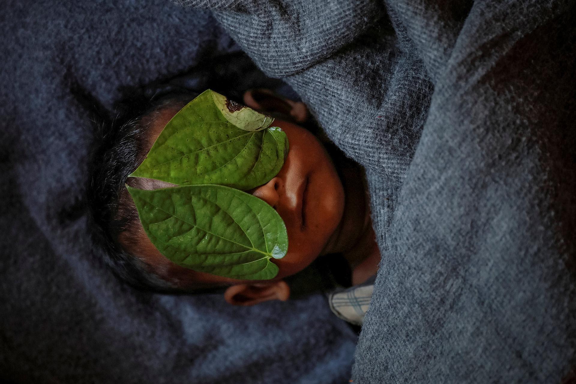 Cubren la cara de Abdul Aziz, refugiado rohingya de 11 meses de edad, cuyo cuerpo envuelto yacía en su refugio familiar después de morir luchando con fiebre alta y tos en el campo de refugiados de Balukhali cerca de Cox's Bazar, Bangladesh, 4 de diciembre de 2017. ( Damir Sagolj)