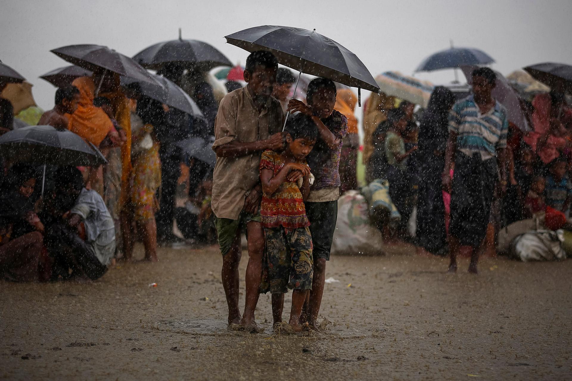 Los refugiados rohingya intentan resguardarse de la lluvia torrencial mientras están en poder de la Guardia Fronteriza de Bangladesh (BGB) después de cruzar ilegalmente la frontera, en Teknaf, Bangladesh, el 31 de agosto de 2017. (Mohammad Ponir Hossain)