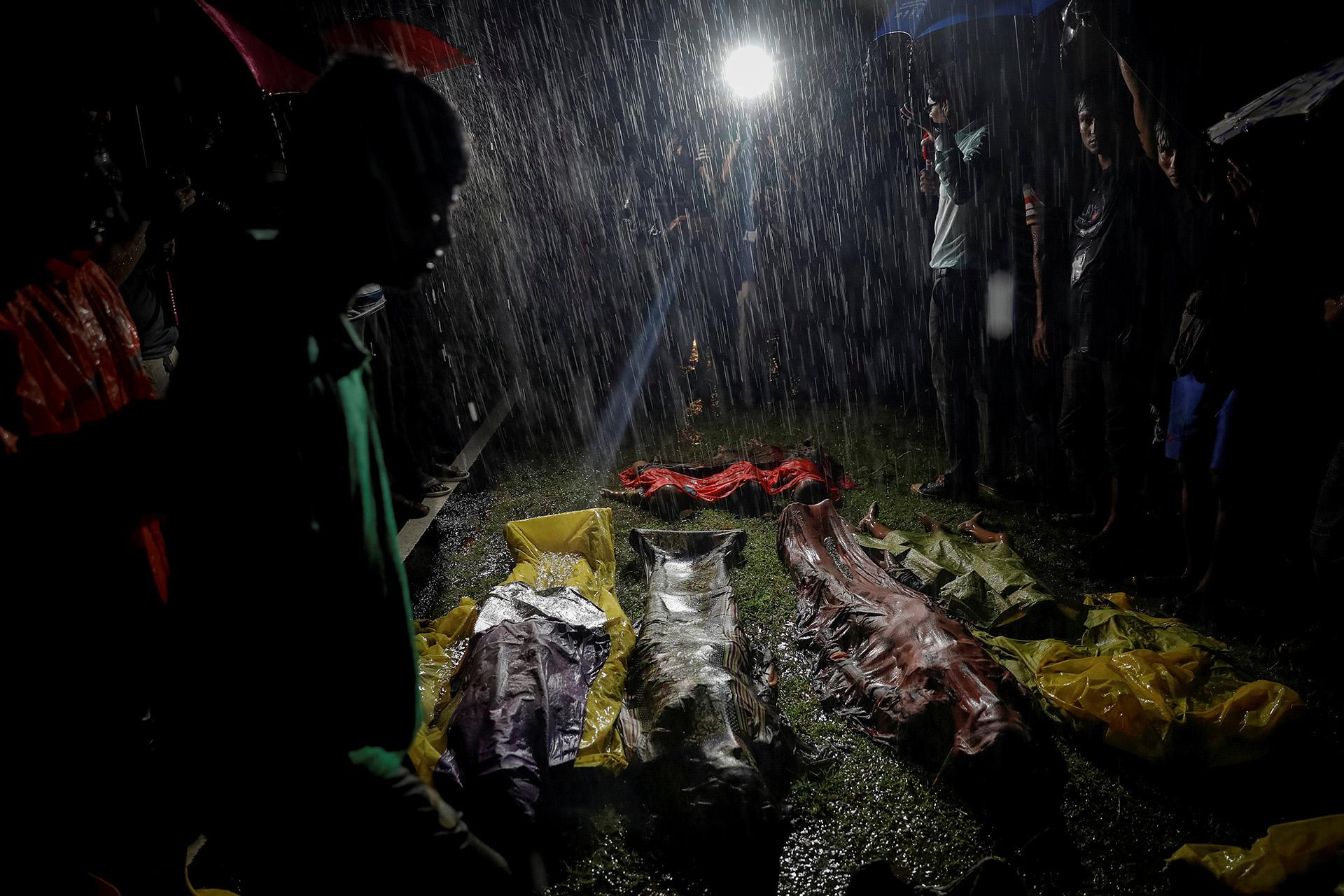 La gente se junta bajo fuertes lluvias alrededor de cuerpos de refugiados Rohingya después de que el bote que usaban para huir de la violencia en Myanmar se hundiera en Inani Beach cerca de Cox's Bazar, Bangladesh 28 de septiembre de 2017. (Damir Sagolj)