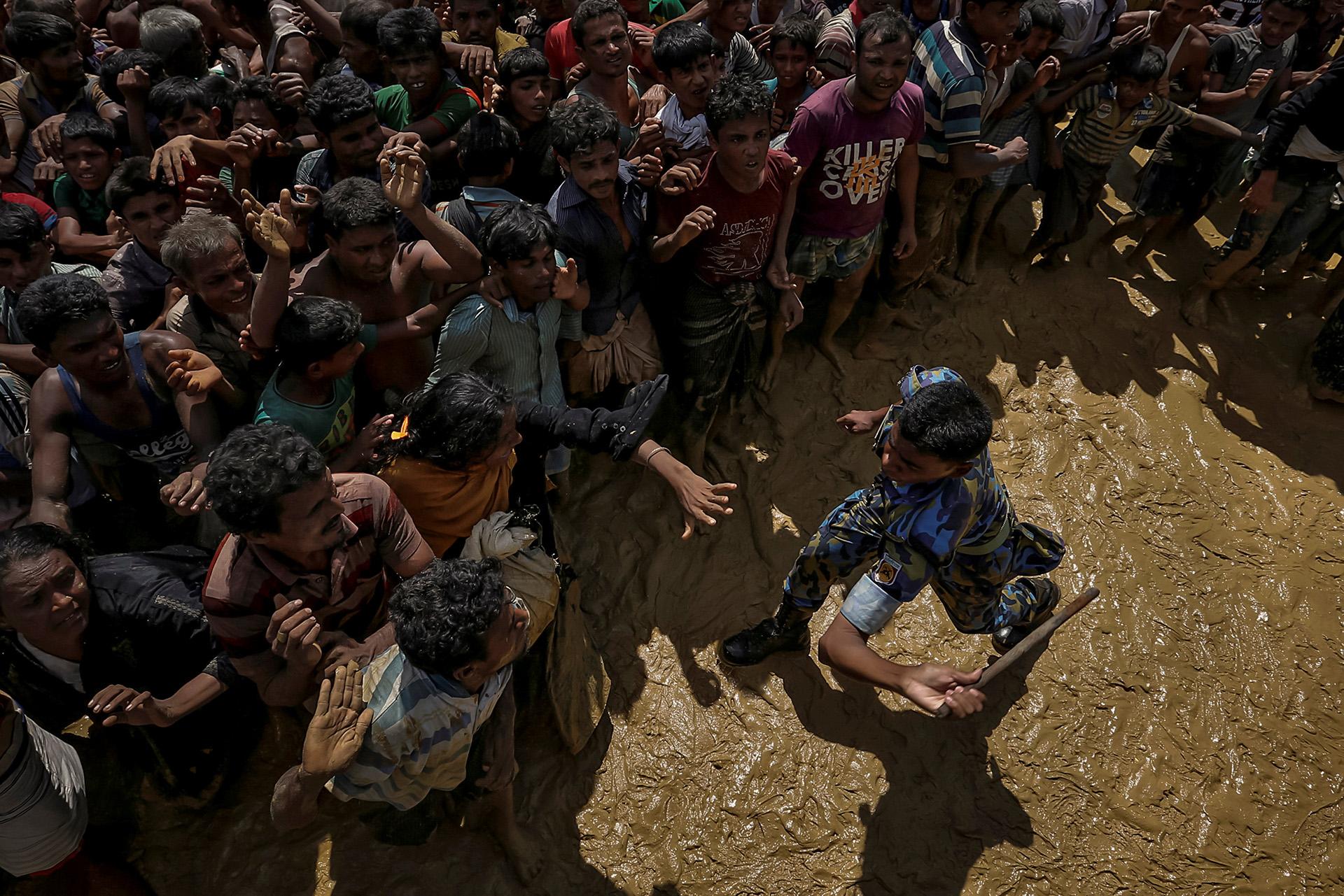 Un oficial de seguridad intenta controlar a los refugiados rohingya que esperan recibir ayuda en Cox's Bazar, Bangladesh, el 21 de septiembre de 2017. (Cathal McNaughton)