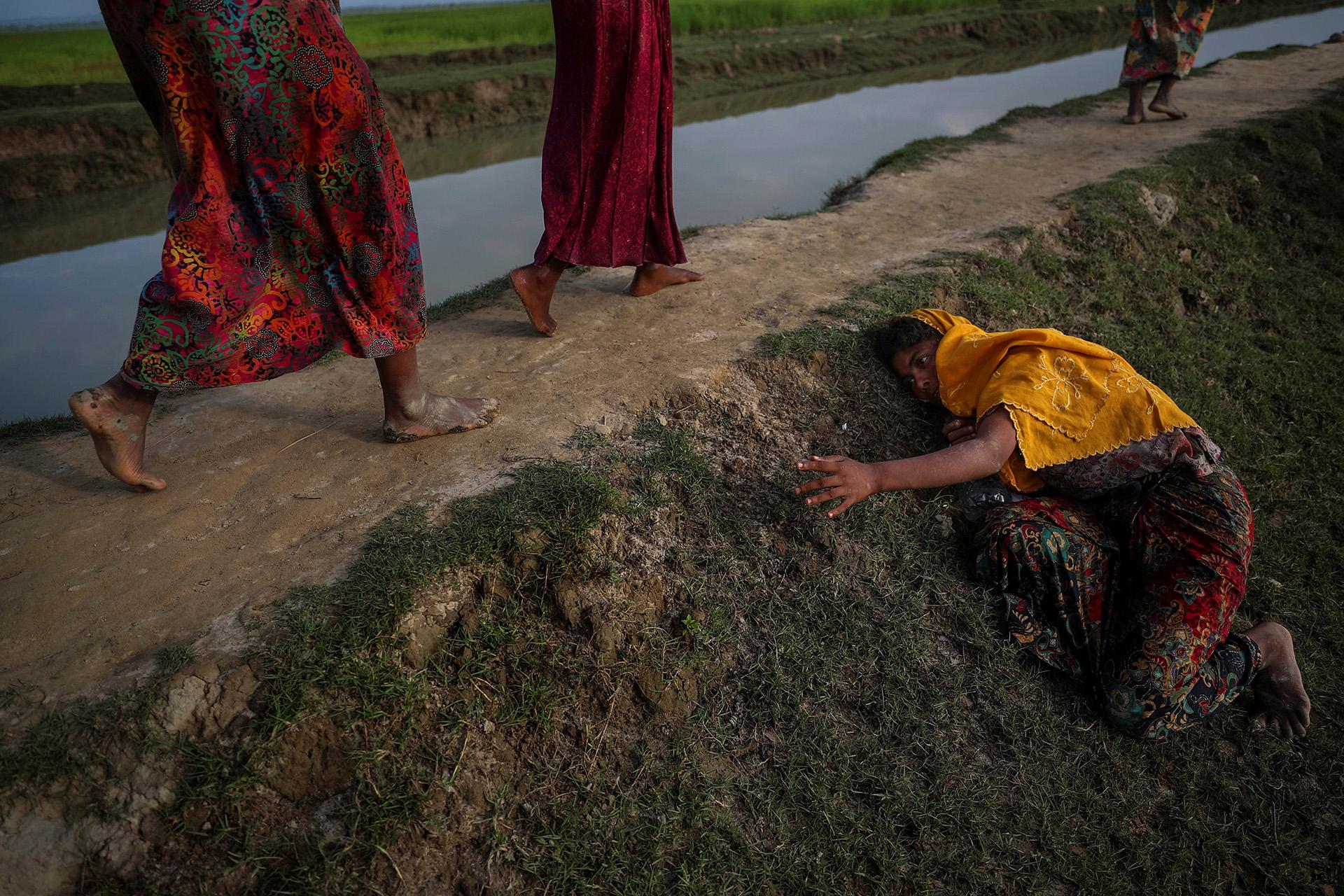 Un agotado refugiado rohingya que huye de la violencia en Myanmar pide ayuda a otros que cruzan hacia Palang Khali, cerca de Cox's Bazar, Bangladesh, el 2 de noviembre de 2017. (Hannah McKay)