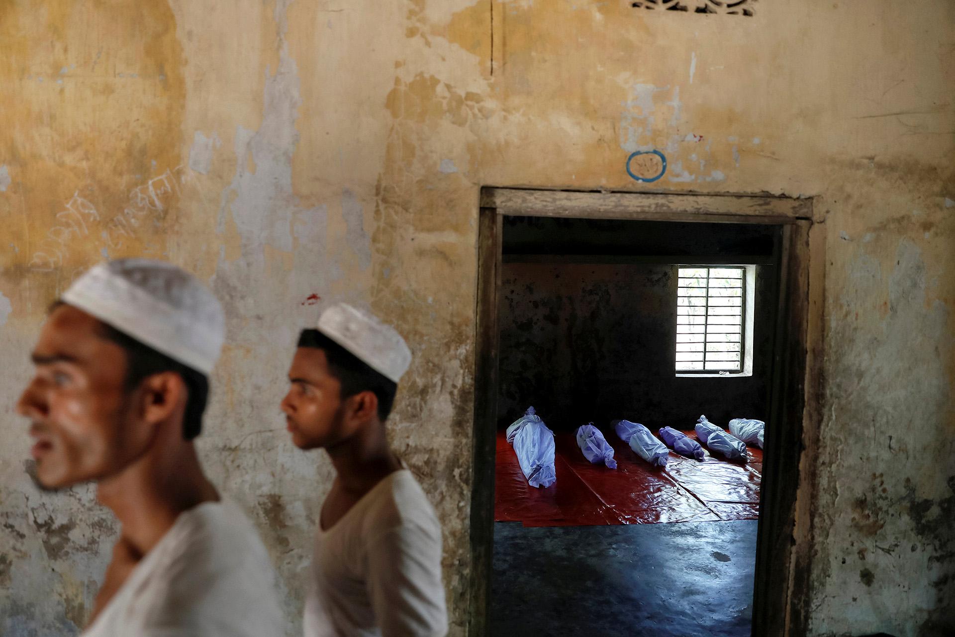 Cuerpos de refugiados Rohingya, que murieron cuando su bote se volcó al huir de Myanmar, son colocados en una madrasa local en Shah Porir Dwip, en Teknaf, cerca de Cox's Bazar en Bangladesh, el 9 de octubre de 2017. (Damir Sagolj)