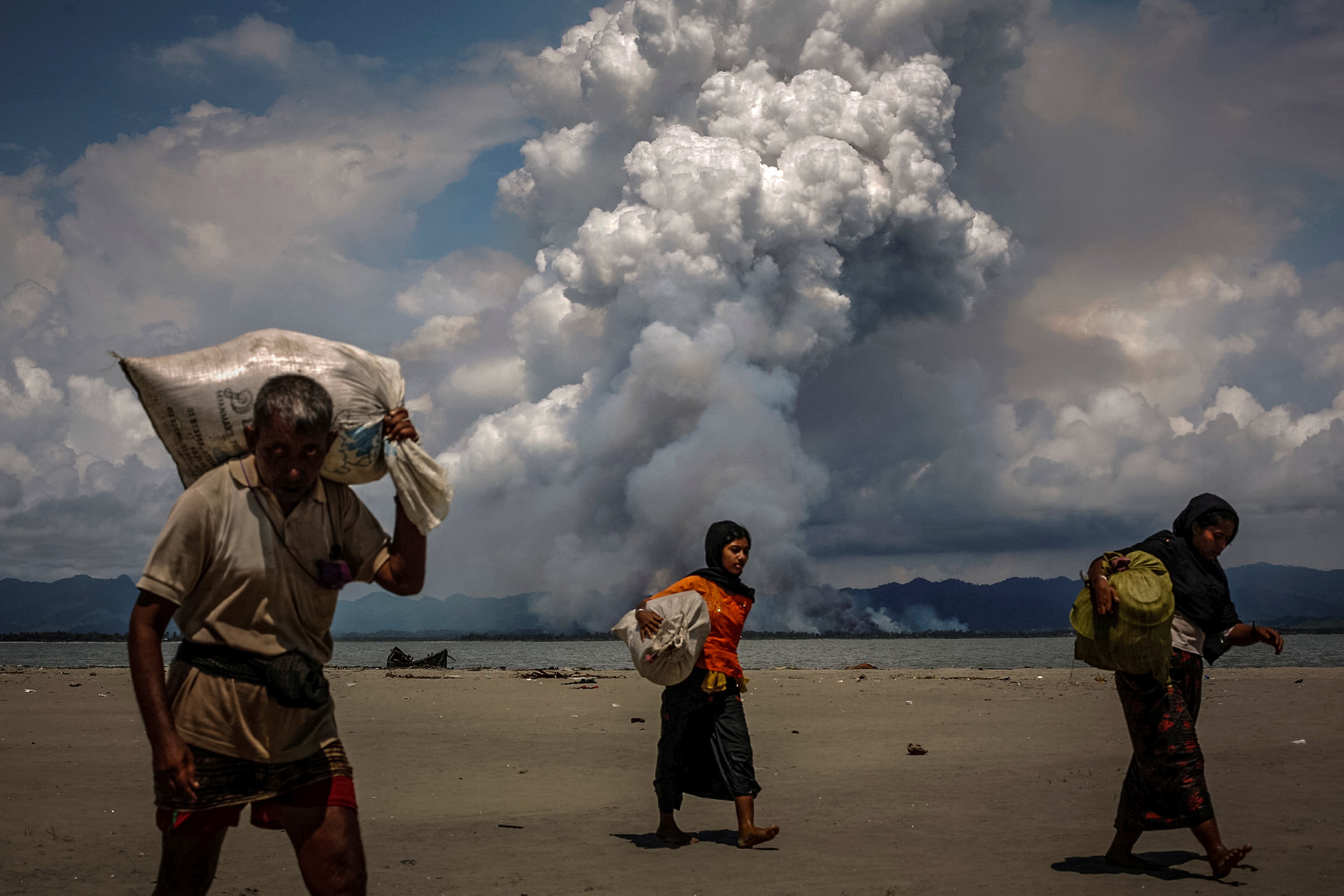 Se ve humo en la frontera de Myanmar cuando los refugiados rohingya caminan por la orilla después de cruzar la frontera entre Bangladesh y Myanmar en barco por la Bahía de Bengala, en Shah Porir Dwip, Bangladesh, el 11 de septiembre de 2017. (Danish Siddiqui)