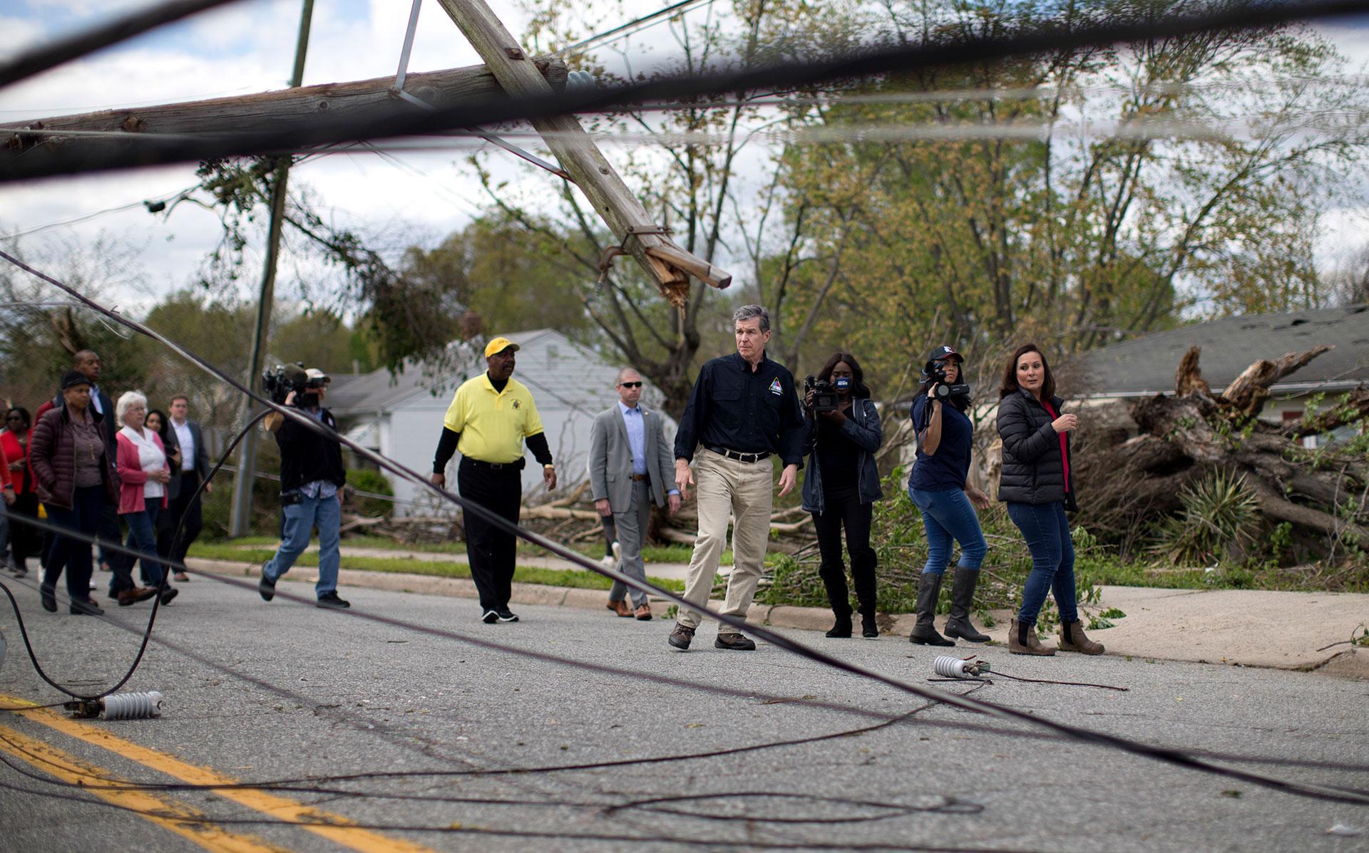 El gobernador de North Carolina Roy Cooper observa un poste de electricidad caído en medio de la calle McConnel de Greensboro